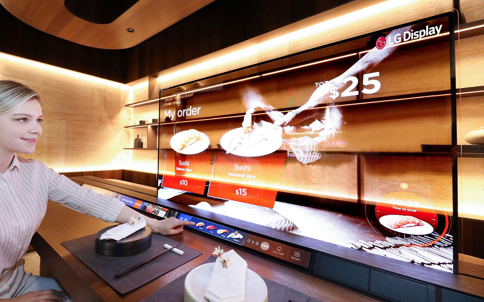 LG Display還在餐廳區的CES 2021上為其客戶提供了改變遊戲規則的地方,壽司吧可以利用55英寸透明OLED顯示屏來提供具有清晰圖像質量的信息,同時受益於高透明性以保持彼此之間的聯繫屏幕兩側的人。 當客人等待他們的訂單時,他們可以觀看電影或電視節目,同時在顯示屏的另一側觀看廚師準備食物。 這種創新產品自然在非接觸式時代更加引人注目,因為它不僅可以充當分區,還可以帶來一些樂趣。