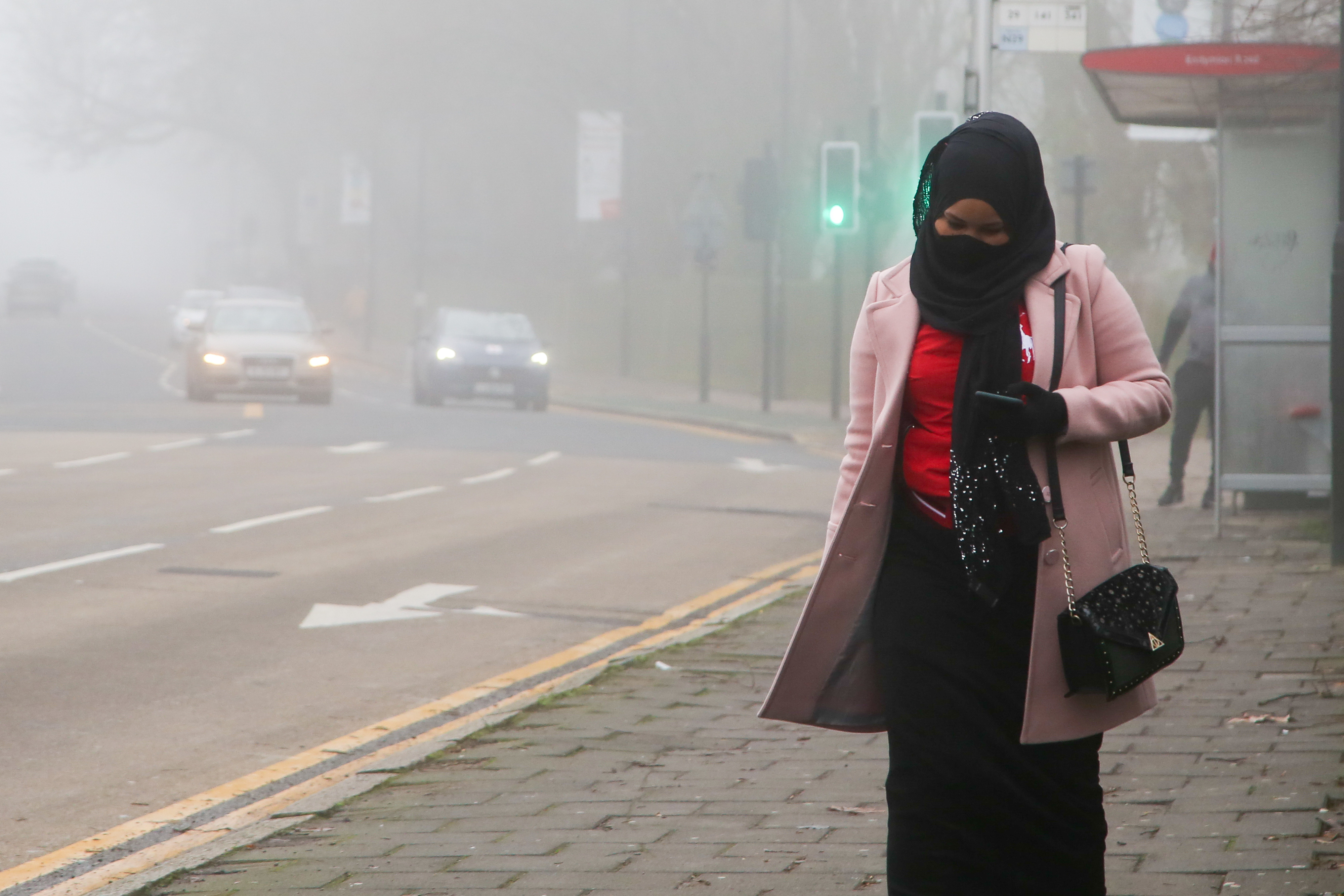 A woman wearing a face mask walks on the street on a foggy morning, as many parts of the UK are now in Tier 4 COVID-19 restrictions. The UK has recorded its highest daily rise in coronavirus cases since the pandemic began with 41,385 positive tests. Prime Minister Boris Johnson hasn't ruled out a national lockdown in the New Year. (Photo by Dinendra Haria / SOPA Images/Sipa USA)