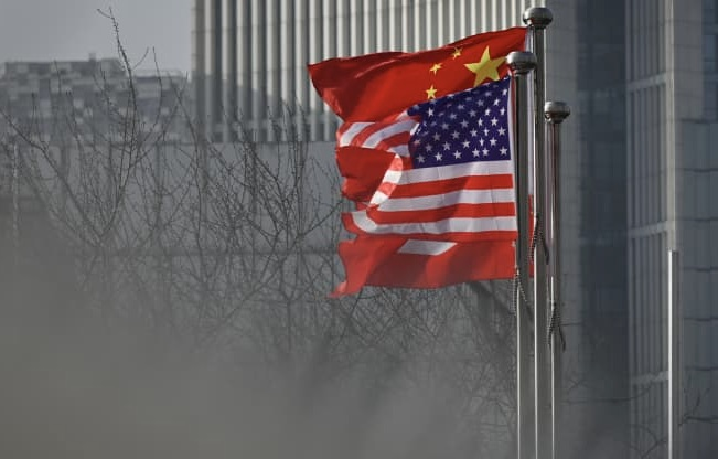 Chinese and U.S. national flags flutter at the entrance of a company office building in Beijing.