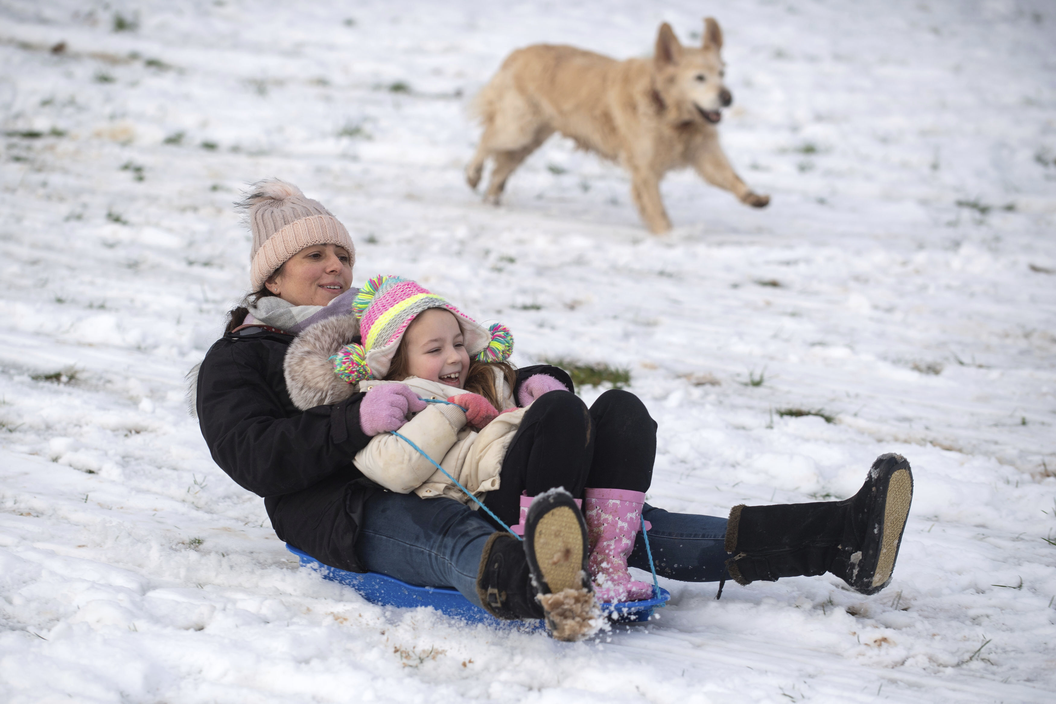 Lizzy and daughter Connie, 6, are chased down a snow covered hill by their golden retriever Pippa in a park in Newcastle-under-Lyme, England, Monday, Dec. 28, 2020. In the aftermath of Storm Bella swathes of the UK are braced for a cold snap, with snow and ice warnings in force across the country. (Joe Giddens/PA via AP)