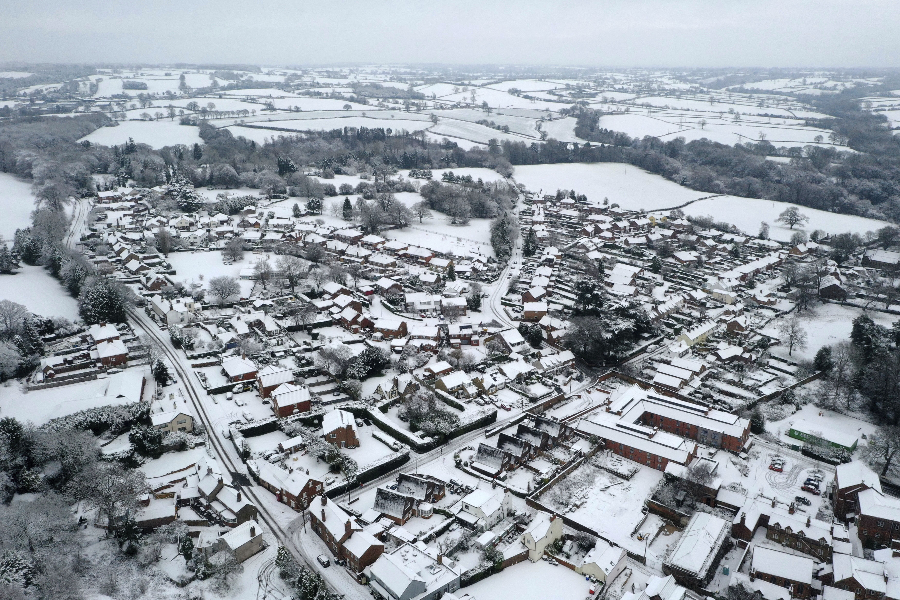 An aerial view of snow covered houses in the village of Oulton in Staffordshire, England, Monday, Dec. 28, 2020. In the aftermath of Storm Bella swathes of the UK are braced for a cold snap, with snow and ice warnings in force across the country. (Tom Leese/PA via AP)