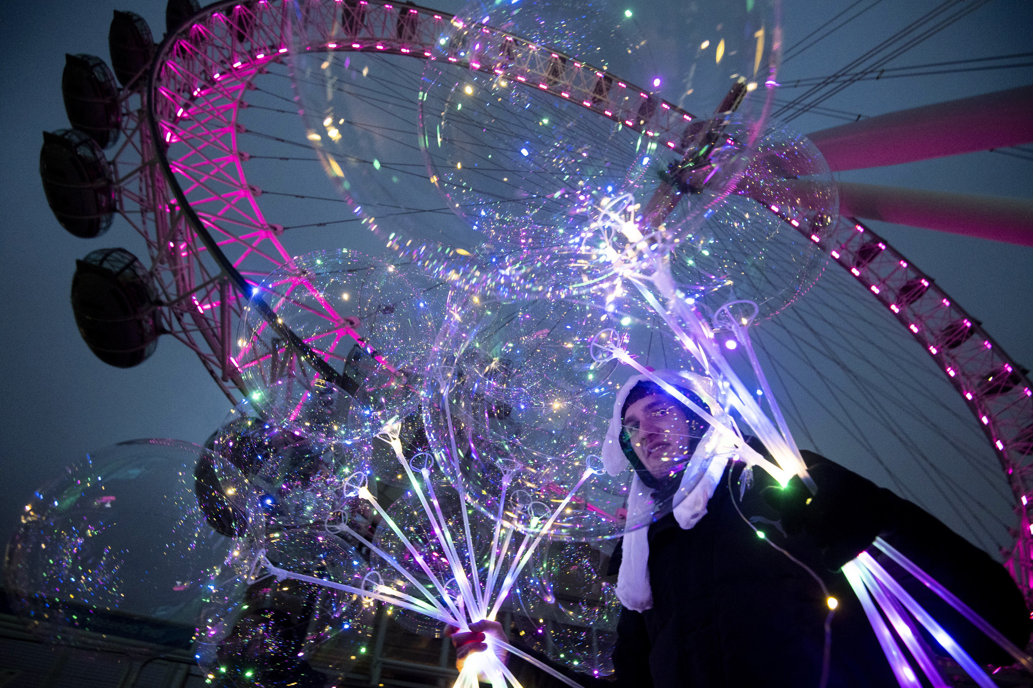 A man holds illuminated balloons, standing in front of the London Eye tourist sightseeing wheel in London, Monday Dec. 28, 2020.  Millions more people moved to harsher coronavirus restrictions as the new tier changes came into force over much of England. (Victoria Jones/PA via AP)