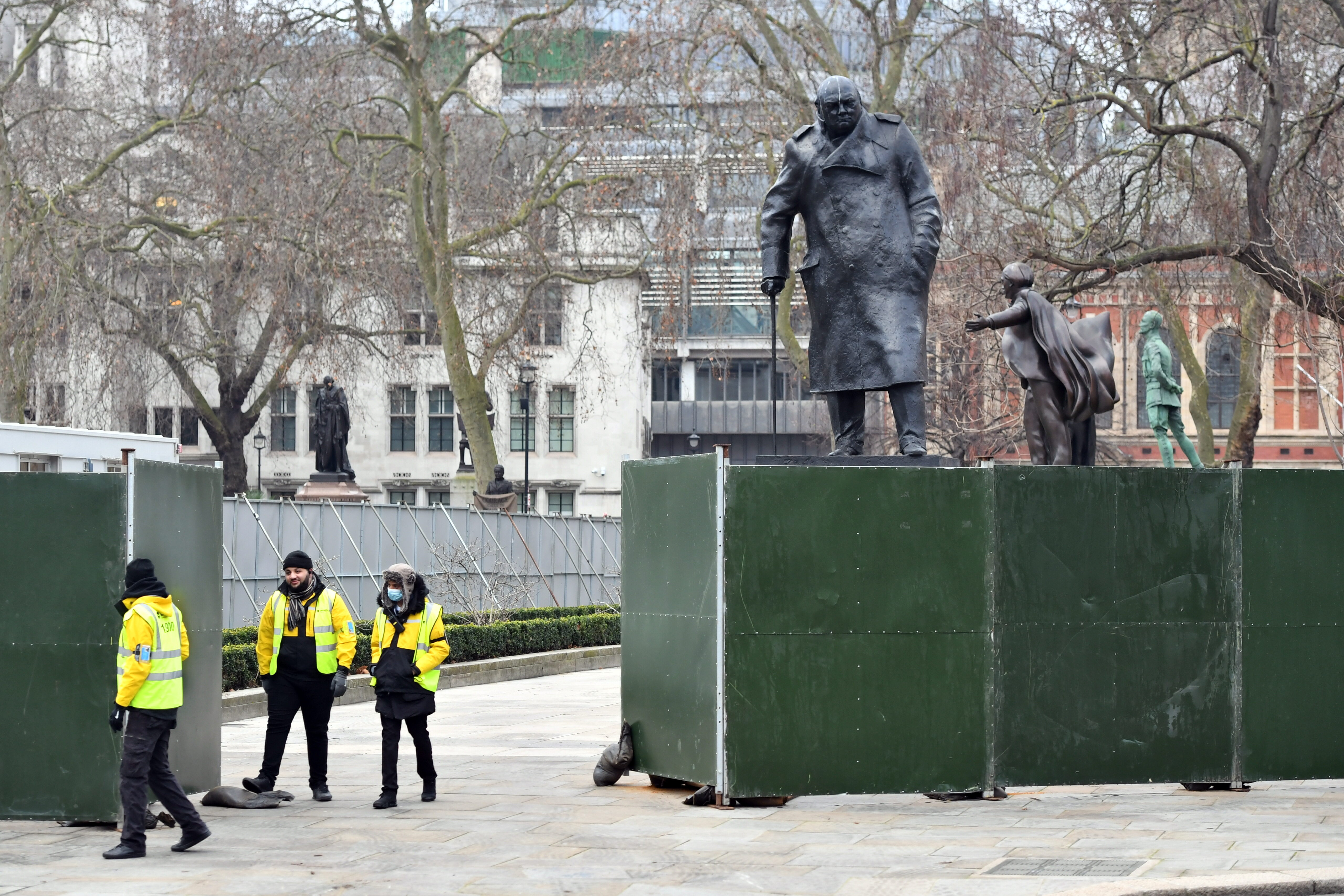 """Fencing around the Winston Churchill statue in Parliament Square, London, ahead of New Year's Eve celebrations. People are being urged to stay home on New Year's Eve to prevent the """"dire"""" situation in hospitals from getting worse. (Photo by Dominic Lipinski/PA Images via Getty Images)"""