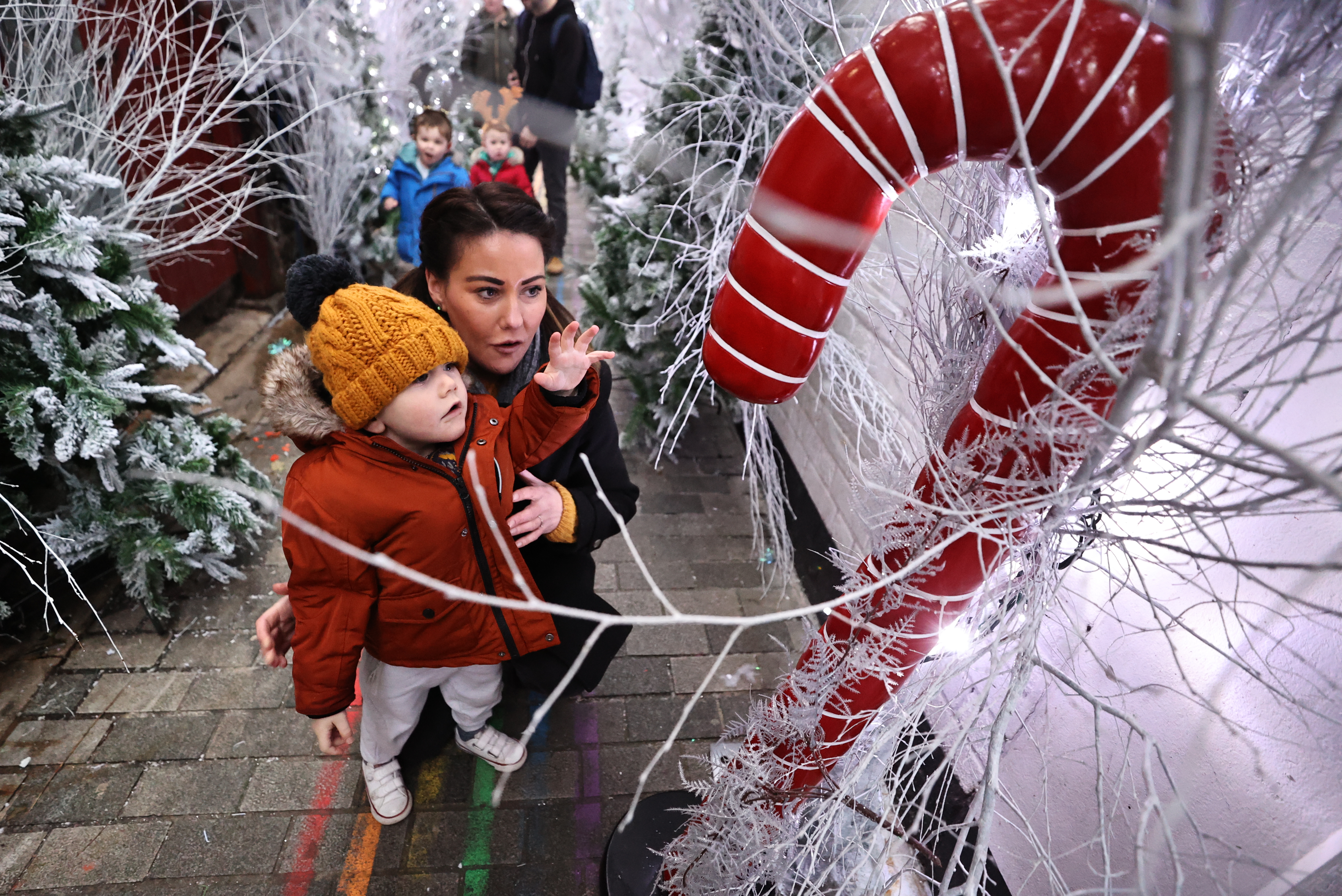 Two year old Antoin McCready walking through The Jailhouse Christmas Magic on Joy's Entry in Belfast with his mother Patricia Williamson. (Photo by Liam McBurney/PA Images via Getty Images)