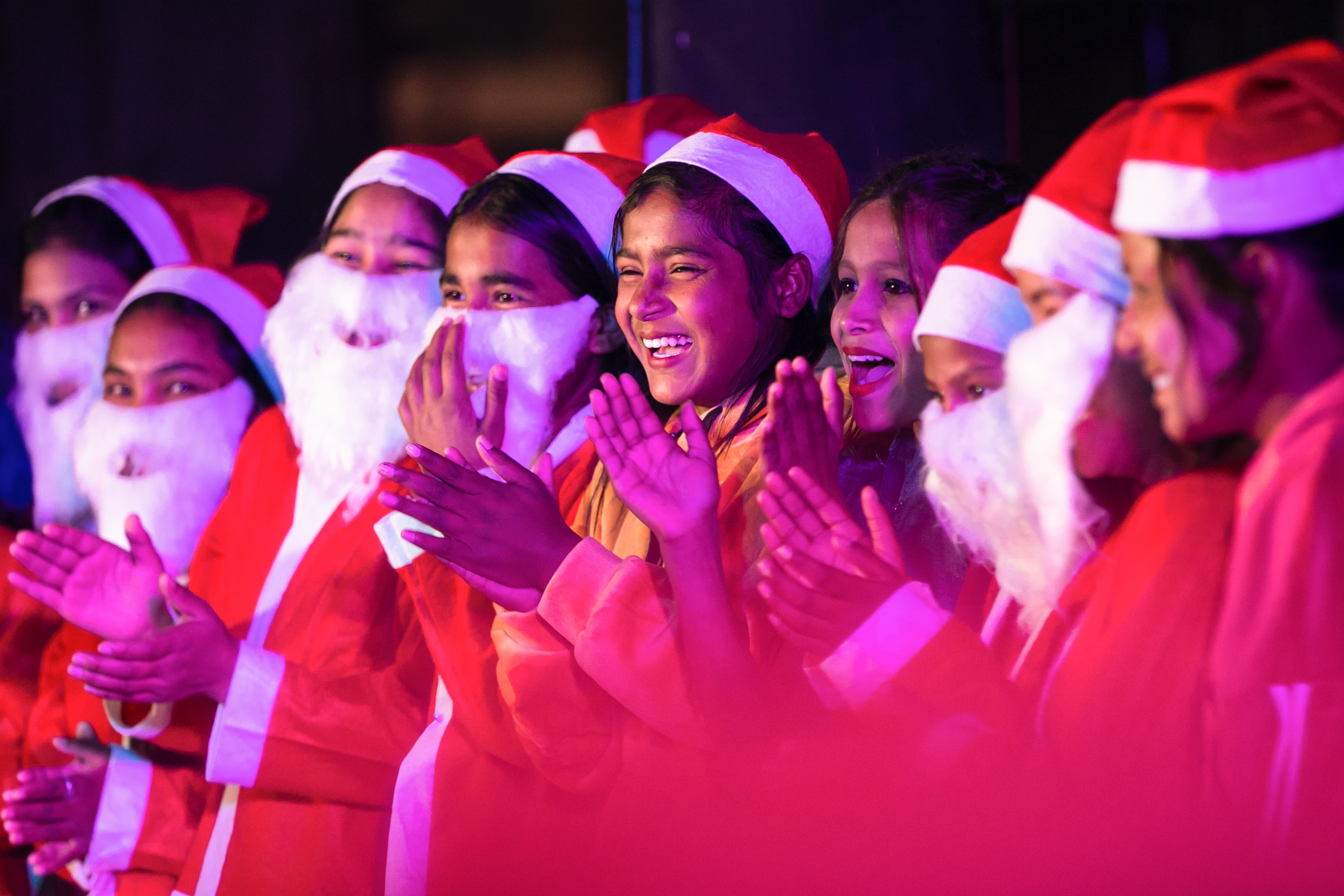 KATHMANDU, NEPAL - 2020/12/24: Nepalese boys and girls dressed as Santa Claus takes part in the Christmas carols as they celebrate Christmas eve at HCM Church. Christmas Eve is the evening or entire day before Christmas Day, the festival commemorating the birth of Jesus Christ. Christmas Day is observed around the world. (Photo by Prabin Ranabhat/SOPA Images/LightRocket via Getty Images)