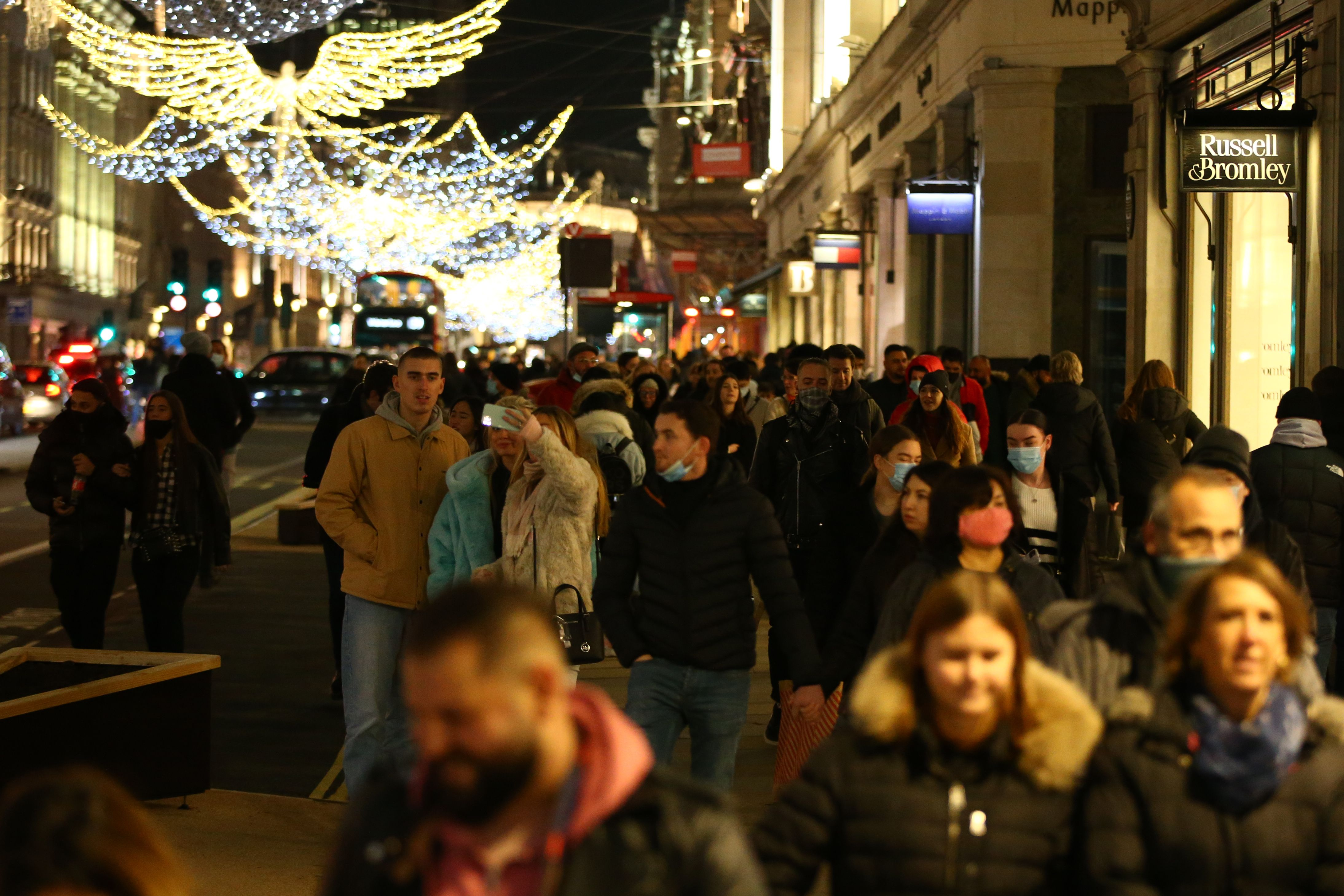 Shoppers walk under the Christmas lights on Regents Street in London on December 6, 2020. - Shoppers returned to Englands high streets this week as shops reopened following the end of a four-week coronavirus lockdown. (Photo by Hollie Adams / AFP) (Photo by HOLLIE ADAMS/AFP via Getty Images)