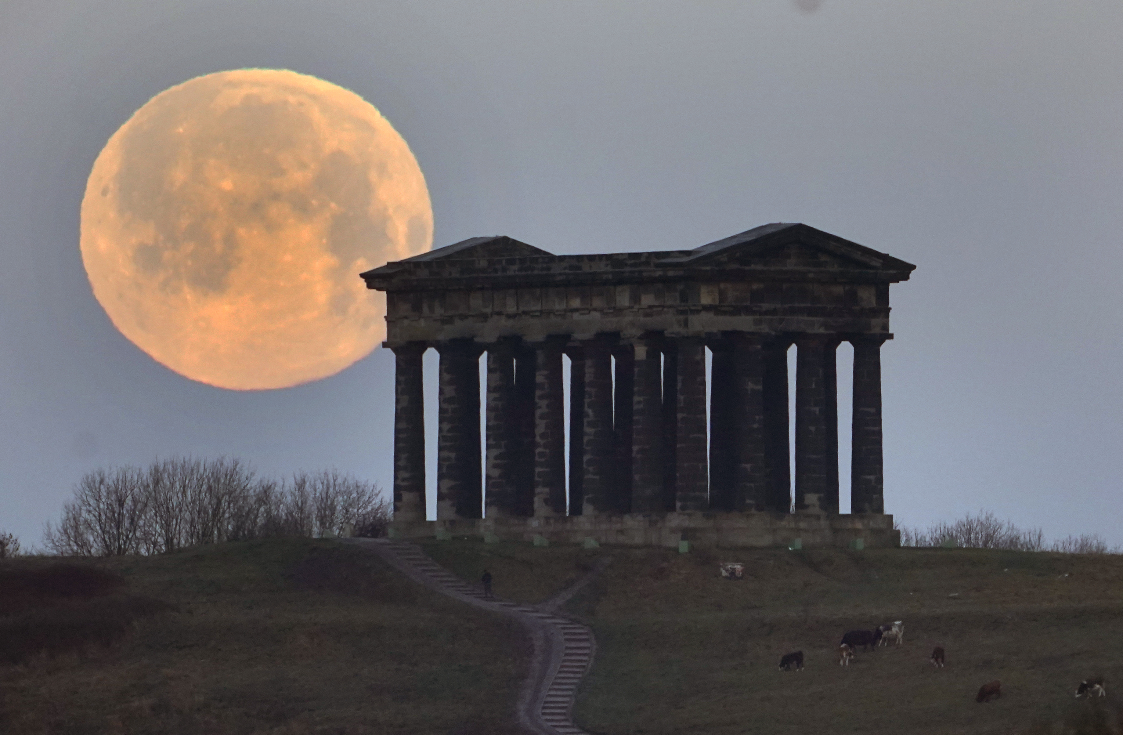The December full moon sets behind the Penshaw Monument, near Sunderland. Elsewhere in the UK, the Met Office issued fresh warnings for snow for Wednesday, with the potential to cause rail and road closures, power cuts, and injuries.