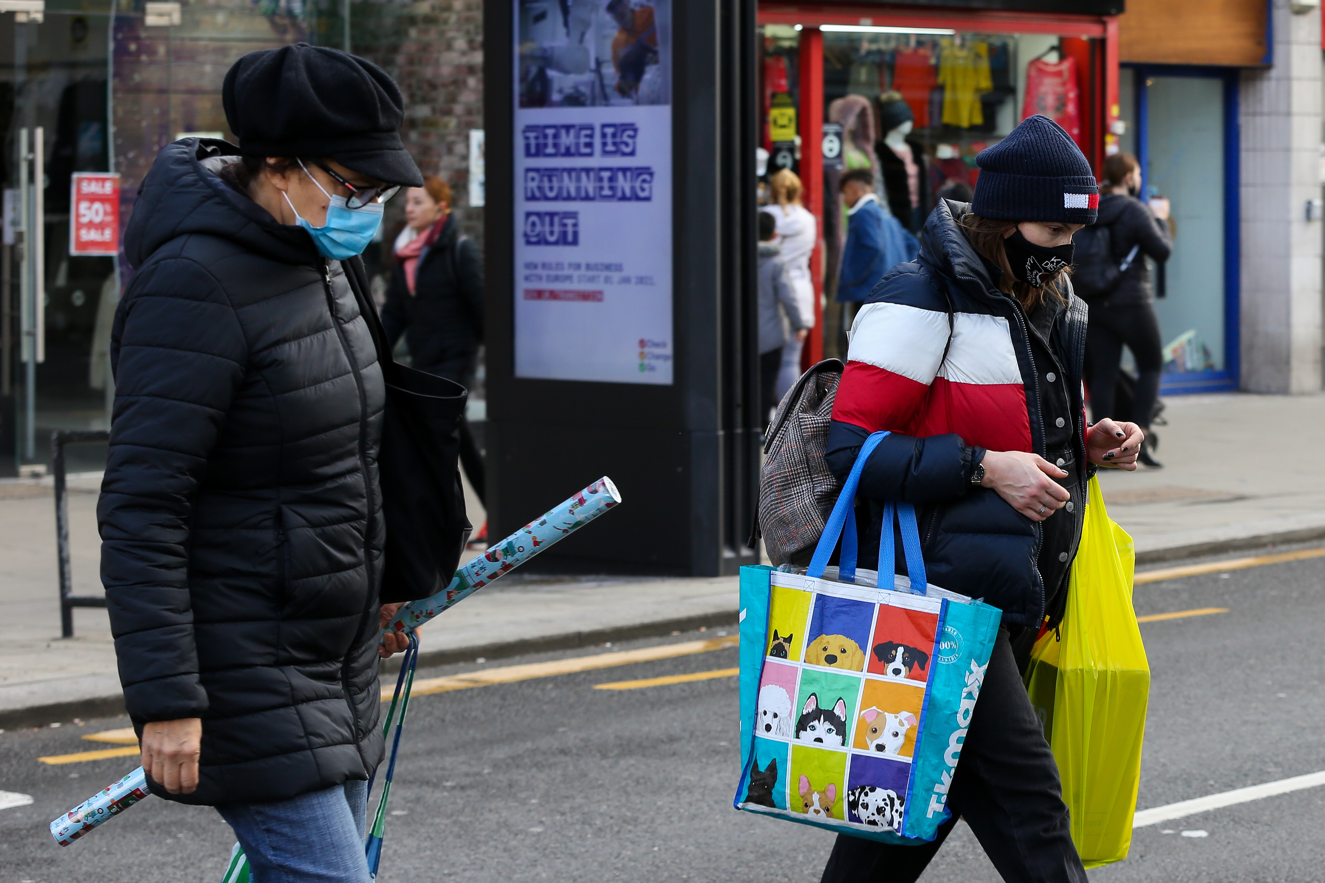 Shoppers wearing face masks walk on the street. Prime Minister Boris Johnson announced on Saturday 19 December, that London and South East of England will move into Tier four restrictions and asked people to 'stay at home'. (Photo by Dinendra Haria / SOPA Images/Sipa USA)
