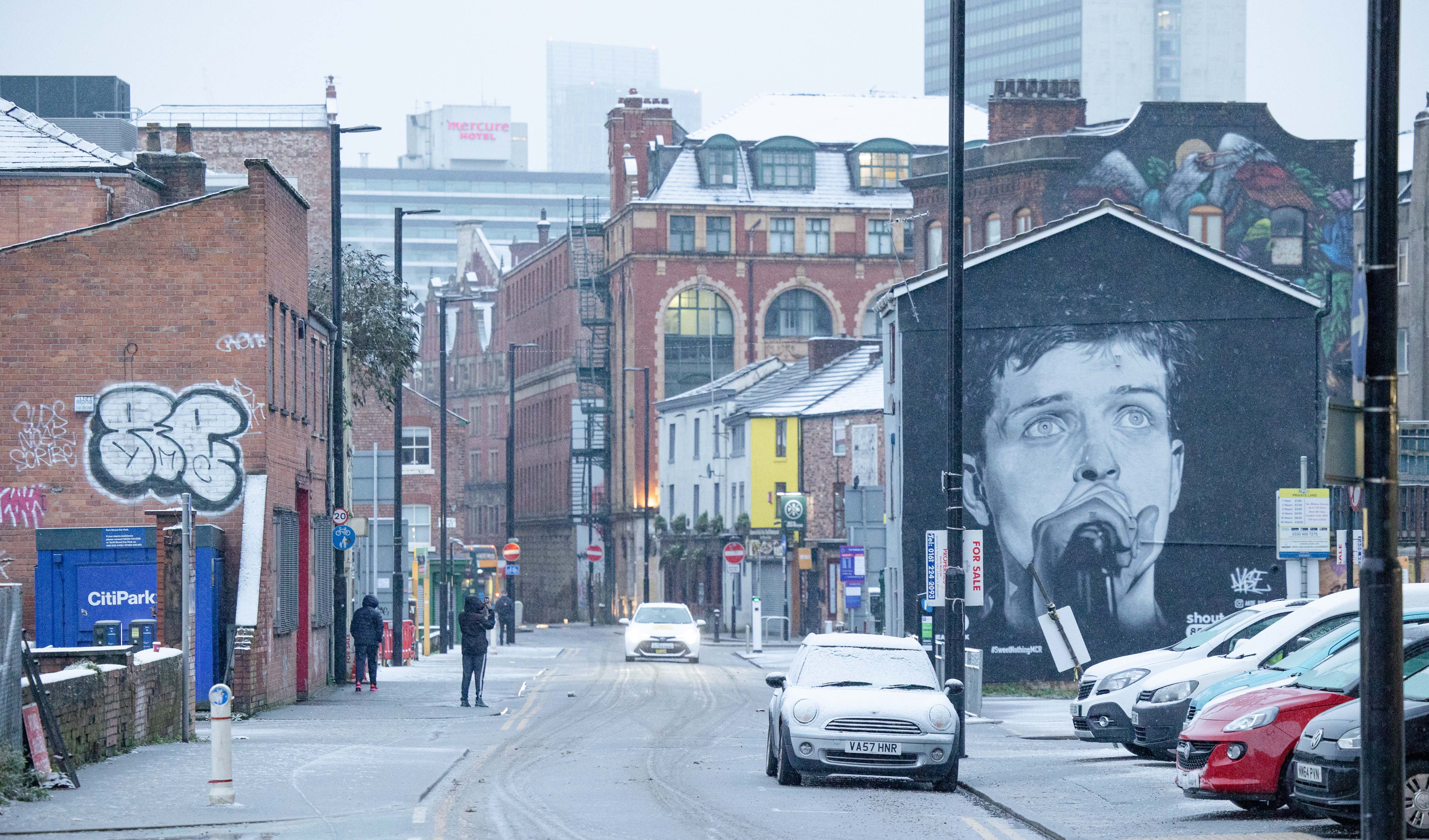 A mural of Joy Division's Ian Curtis watches over the Northern Quarter in Manchester city centre, as snow hits the UK. Tuesday 29th December 2020.  (Photo by Pat Scaasi/MI News/NurPhoto via Getty Images)
