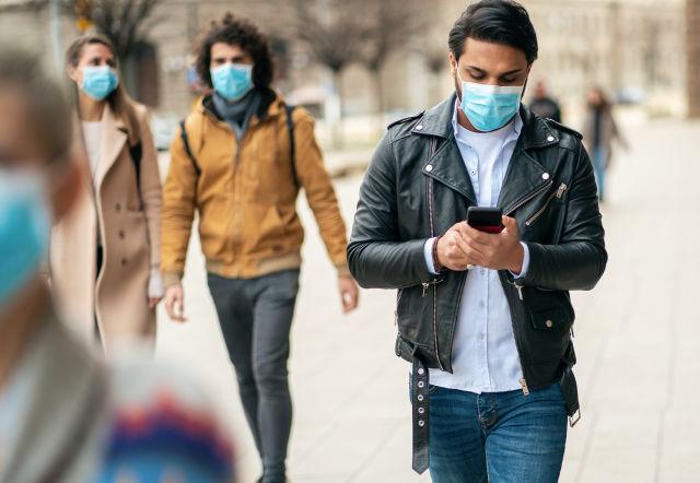 年輕人在街上戴著口罩,以防止冠狀病毒和防煙霧和使用智能手機的肖像