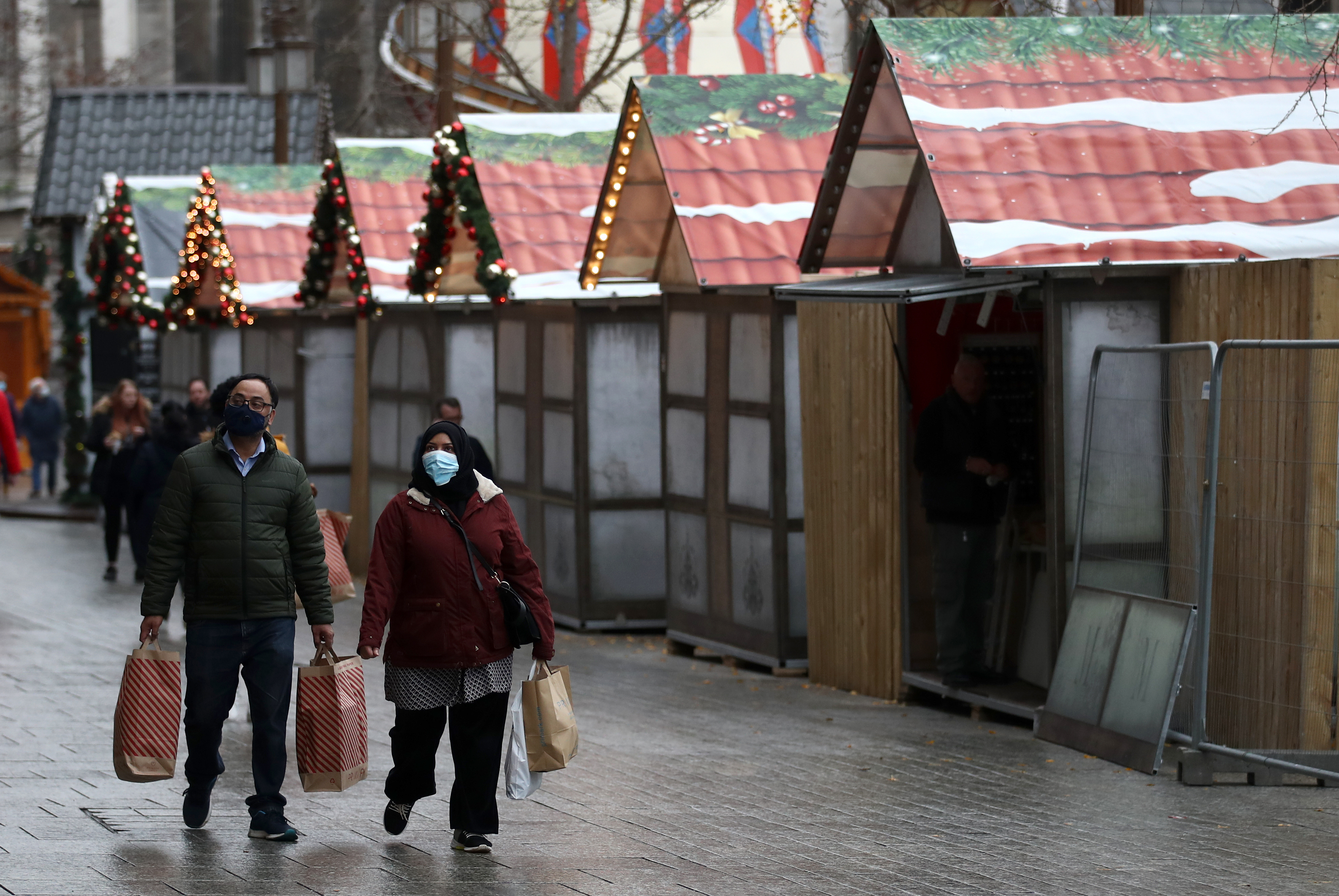 Shoppers walk past the Christmas market being erected in the market square in Nottingham city centre, as non-essential shops in England open their doors to customers for the first time after the second national lockdown ends and England has a strengthened tiered system of regional coronavirus restrictions.