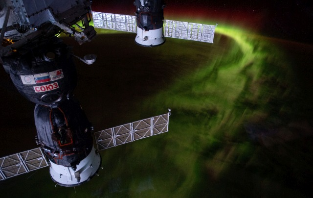 """iss059e099150 (June 8, 2019) --- The International Space Station was orbiting 269 miles above the Indian Ocean southwest of Australia when this nighttime photograph was taken of the aurora australis, or """"southern lights."""" Russia's Soyuz MS-12 crew ship (foreground) and Progress 72 resupply ship are seen in this mesmerizing view."""