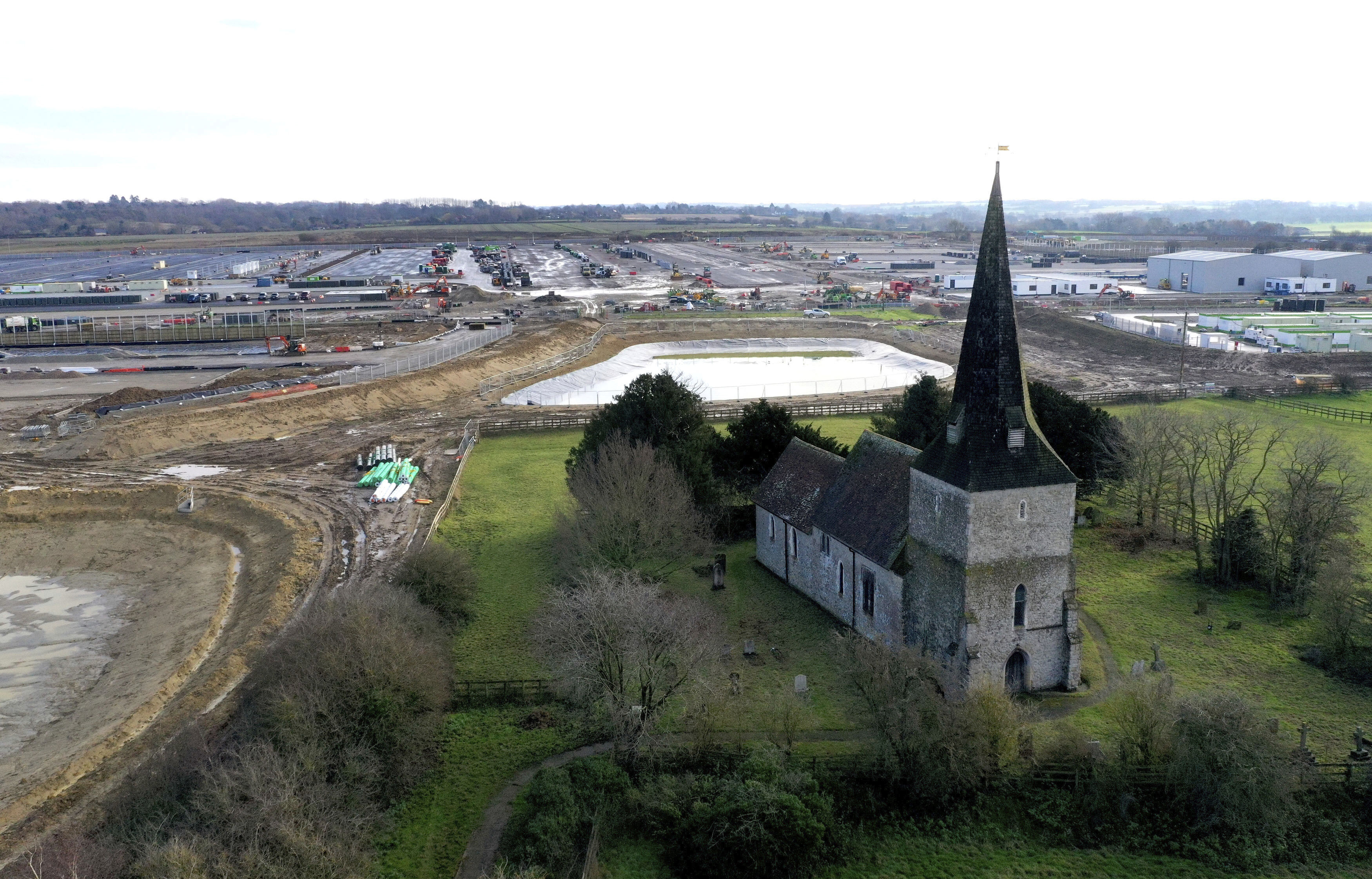 An aerial view of the thirteenth century St. Mary's Church as the British government develops a vast area into a post-Brexit lorry park, in Sevington, southern England, Sunday Nov. 6, 2020.  While diplomatic efforts to strike a Brexit trade deal continue between Britain and the European bloc, preparations are underway to cope with anticipated goods vehicle cross border transport delays. (Gareth Fuller/PA via AP)