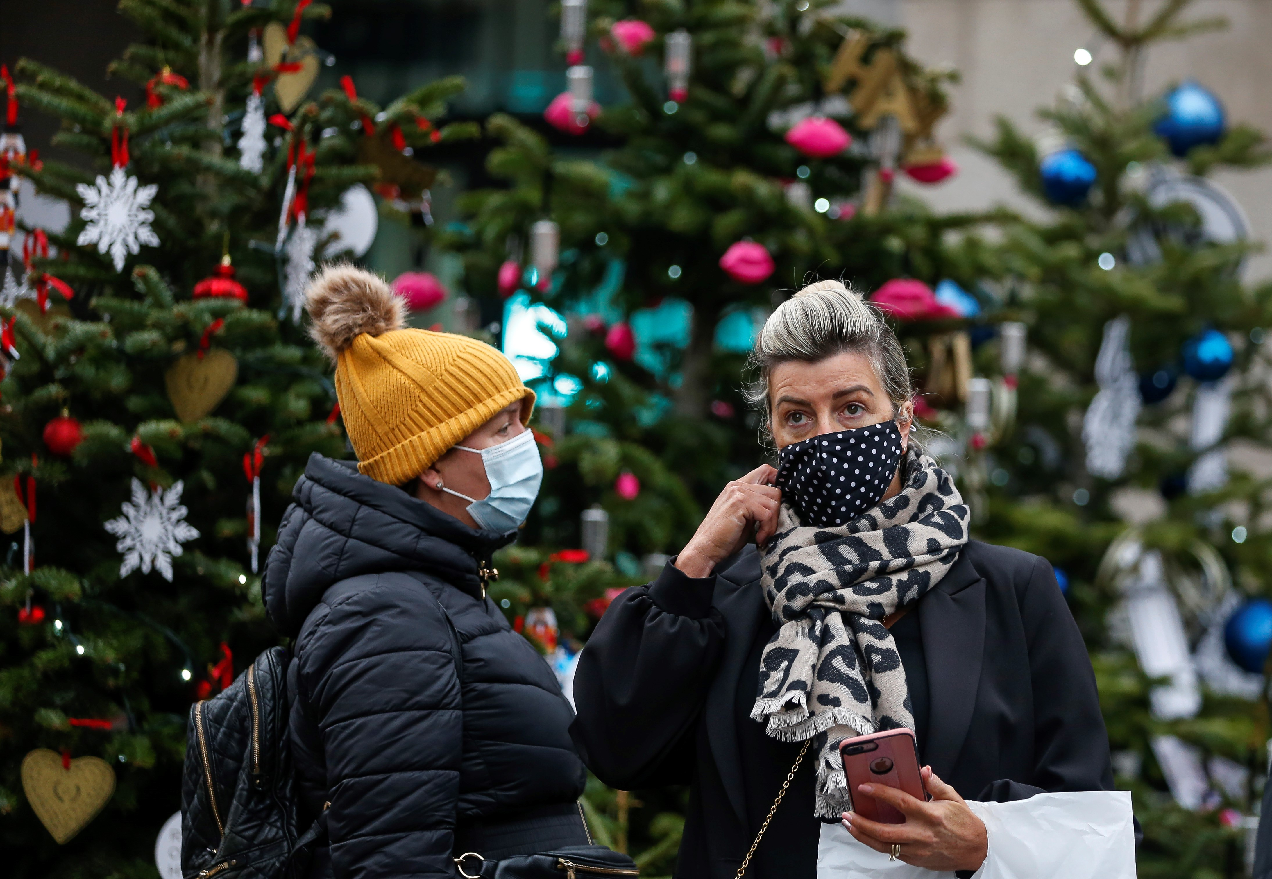 LONDON, Dec. 4, 2020 -- People wearing face masks stand next to Christmas trees in London, Britain, on Dec. 4, 2020. Another 16,298 people in Britain have tested positive for COVID-19, bringing the total number of coronavirus cases in the country to 1,690,432, according to official figures released Friday. The coronavirus-related deaths in Britain rose by 504 to 60,617, the data showed. (Photo by Han Yan/Xinhua via Getty) (Xinhua/Han Yan via Getty Images)