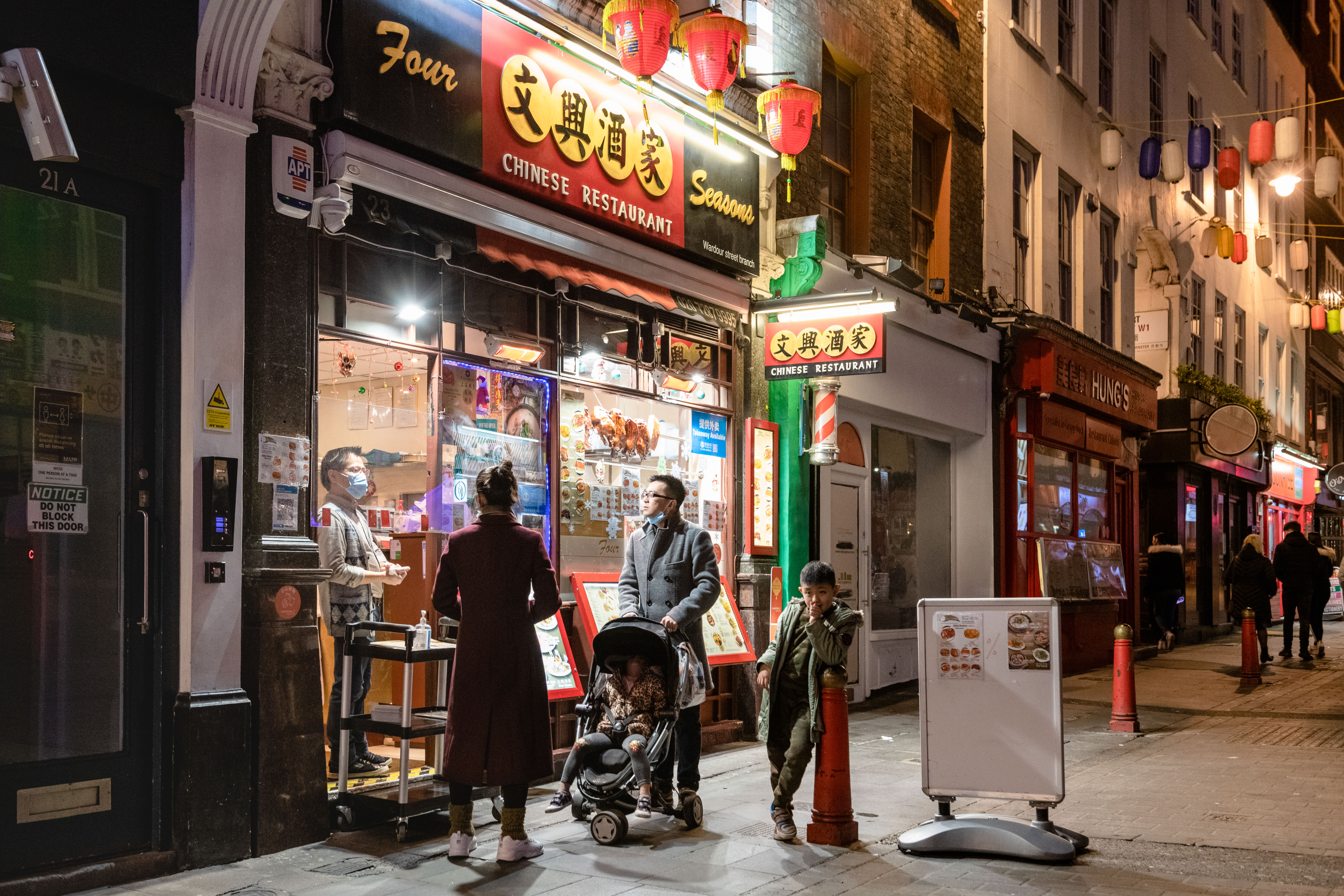 LONDON, ENGLAND - DECEMBER 20:  People order takeout at restaurants in Chinatown on December 20, 2020 in London, England.  London and the South East enter a 'Tier 4' lockdown as a new coronavirus strain is detected in the lead up to Christmas. (Photo by Joseph Okpako/Getty Images)