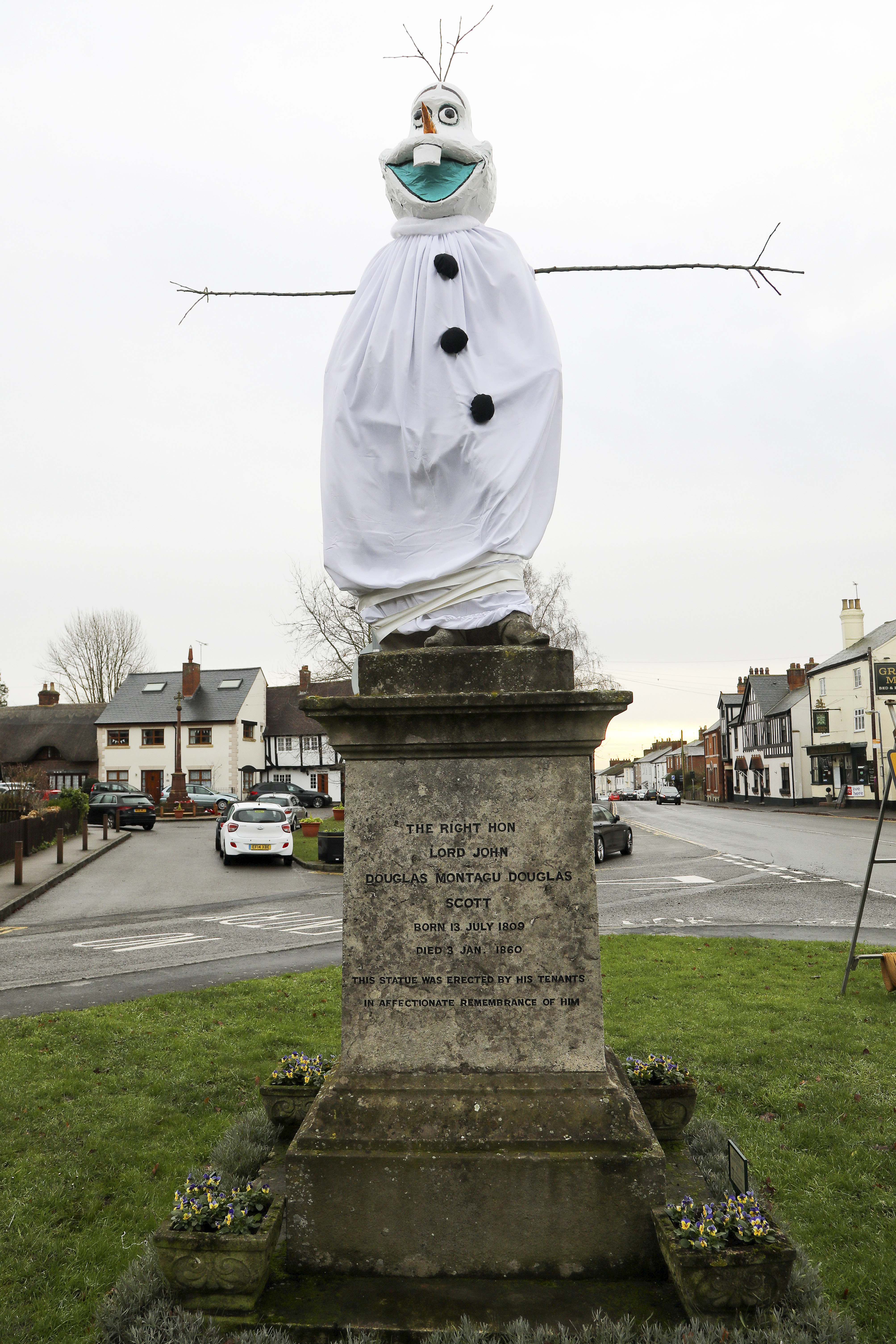 A village is hunting festive pranksters who have turned a statue of its most famous son into PEPPA PIG. The statue of Lord John Scott, who died in 1860, is a Christmas target for jokers in Dunchurch, near Rugby, Warks. Hilarious pictures show the monument draped in a pink sheet with arms stretched out and a huge pink papier mache head resembling kids' TV favourite. The statue has previously been turned into Harry Potter, Shrek, Happy Feet, Pikachu, Homer Simpson, an Olympic athlete and The Grinch in an annual tradition dating back to the 1970s.