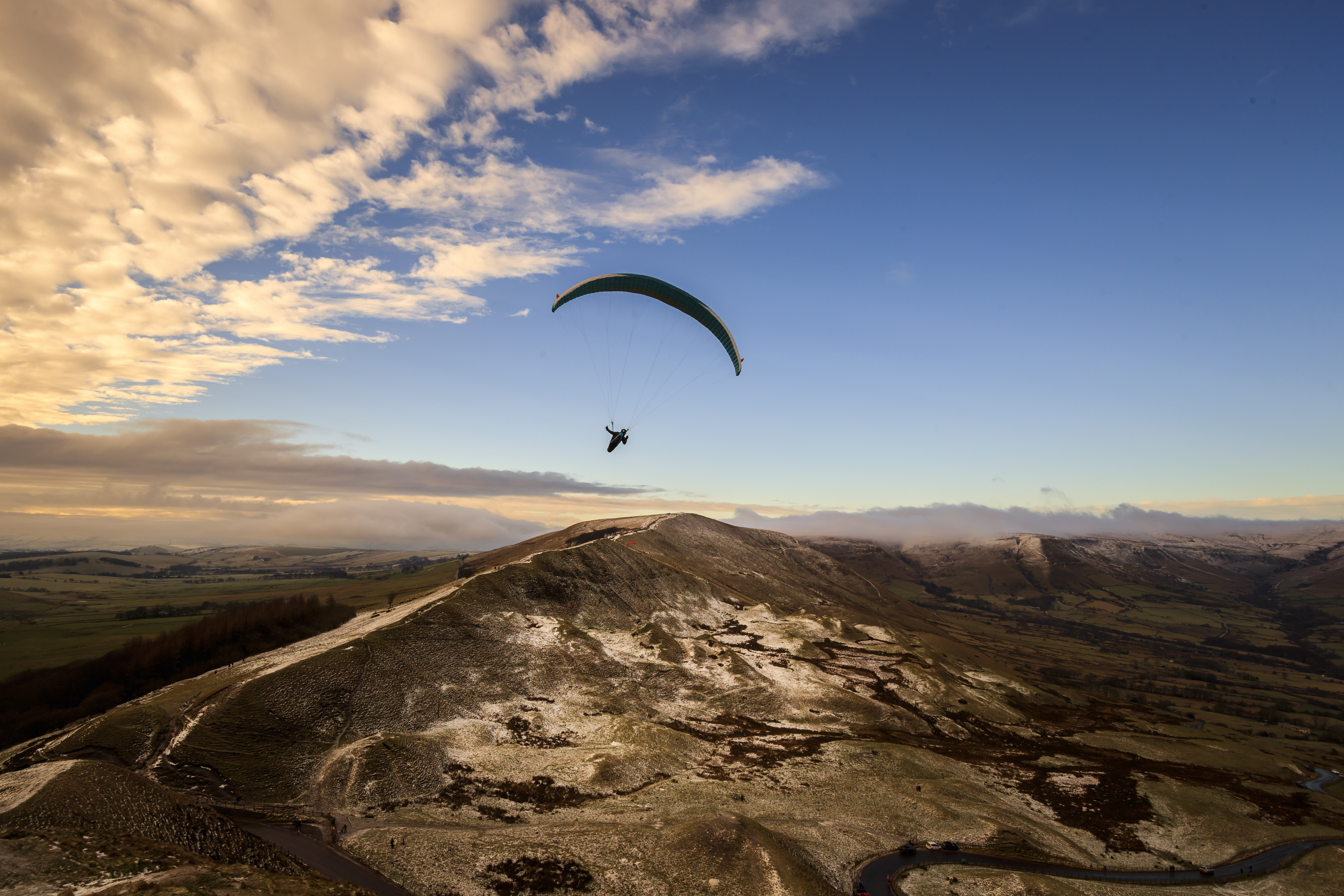 A paraglider flying over Mam Tor, a 517m hill near Castleton in Derbyshire. (Photo by Danny Lawson/PA Images via Getty Images)