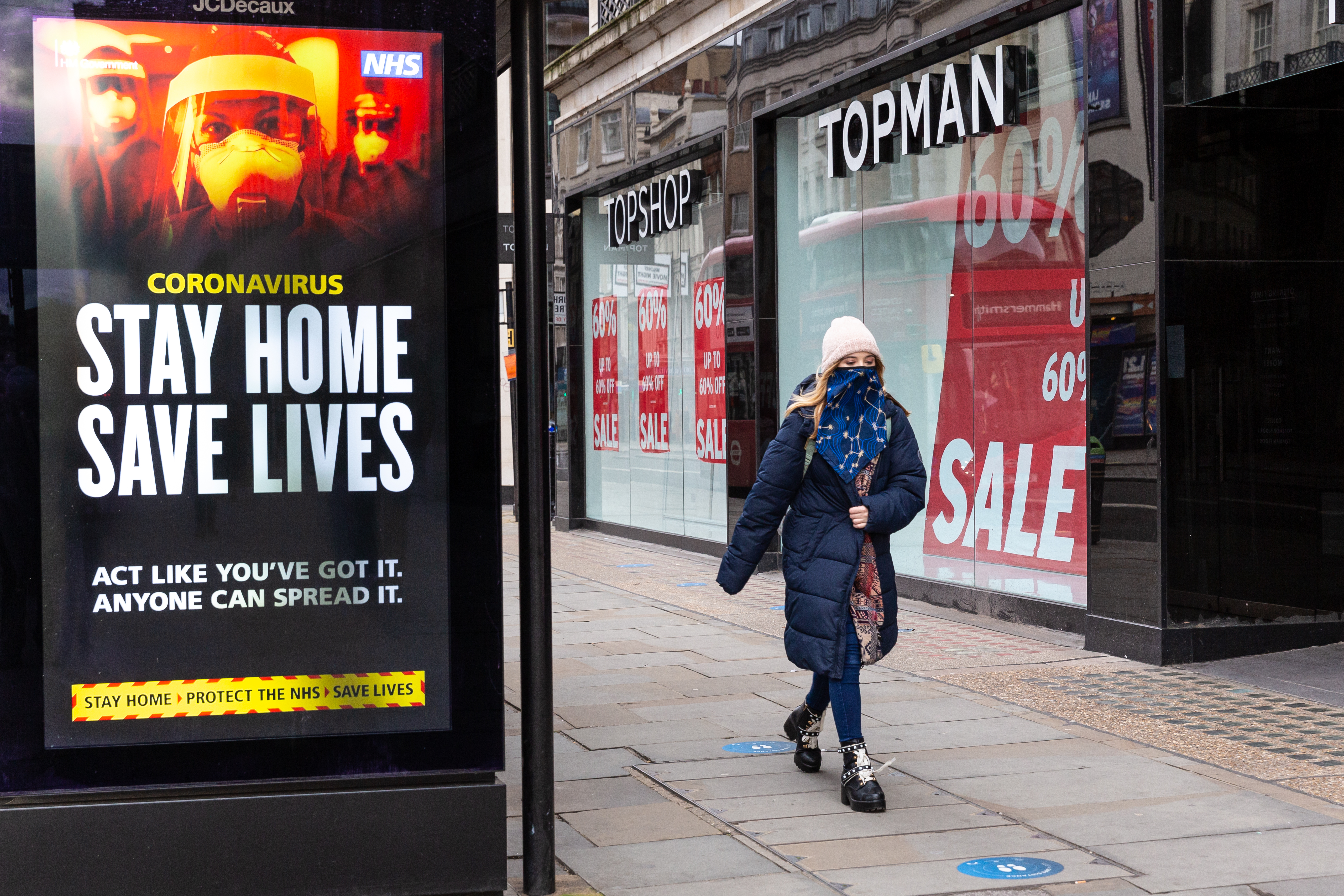 A woman in protective face mask is seen walking by the NHS 'Stay Home' poster as the UK's government introduced strict Coronavirus restrictions earlier this month due to sharp increase in numbers of Covid-19 cases in UK - London, England on January 11, 2021. Exercising  and going to work are the exceptions for Stay at Home policy. (Photo by Dominika Zarzycka/NurPhoto via Getty Images)
