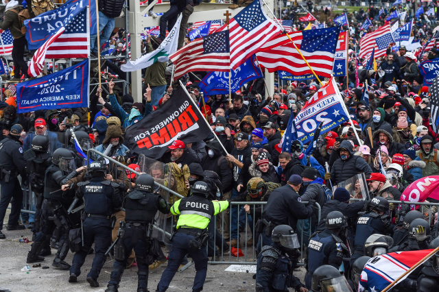 Trump supporters clash with police and security forces as they storm the US Capitol in Washington, DC on January 6, 2021. - Demonstrators breeched security and entered the Capitol as Congress debated the a 2020 presidential election Electoral Vote Certification. (Photo by ROBERTO SCHMIDT / AFP) (Photo by ROBERTO SCHMIDT/AFP via Getty Images)