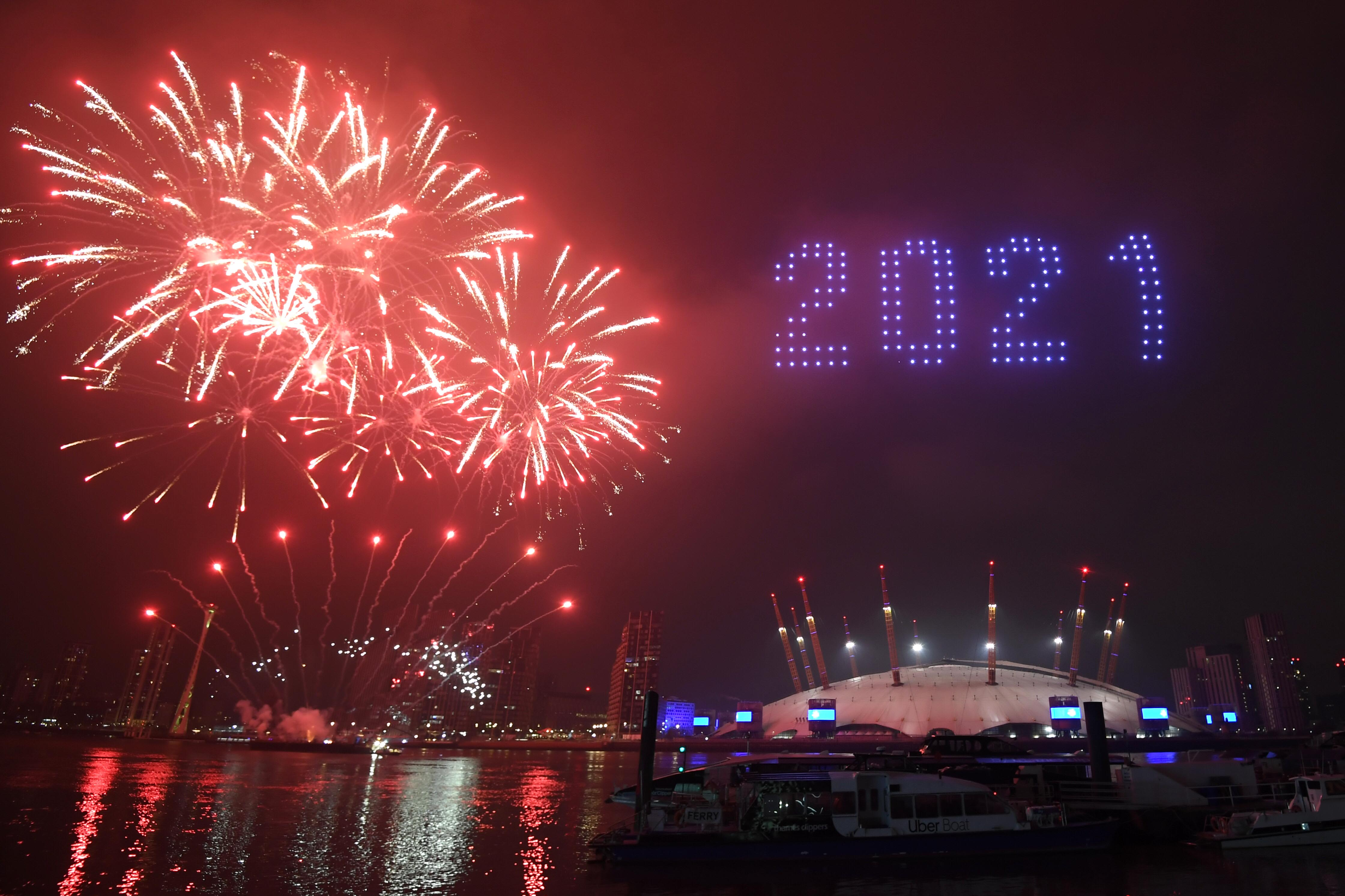 Fireworks and drones illuminate the night sky over the The O2 in London as they form a light display as London's normal New Year's Eve fireworks display was cancelled due to the coronavirus pandemic. (Photo by Victoria Jones/PA Images via Getty Images)