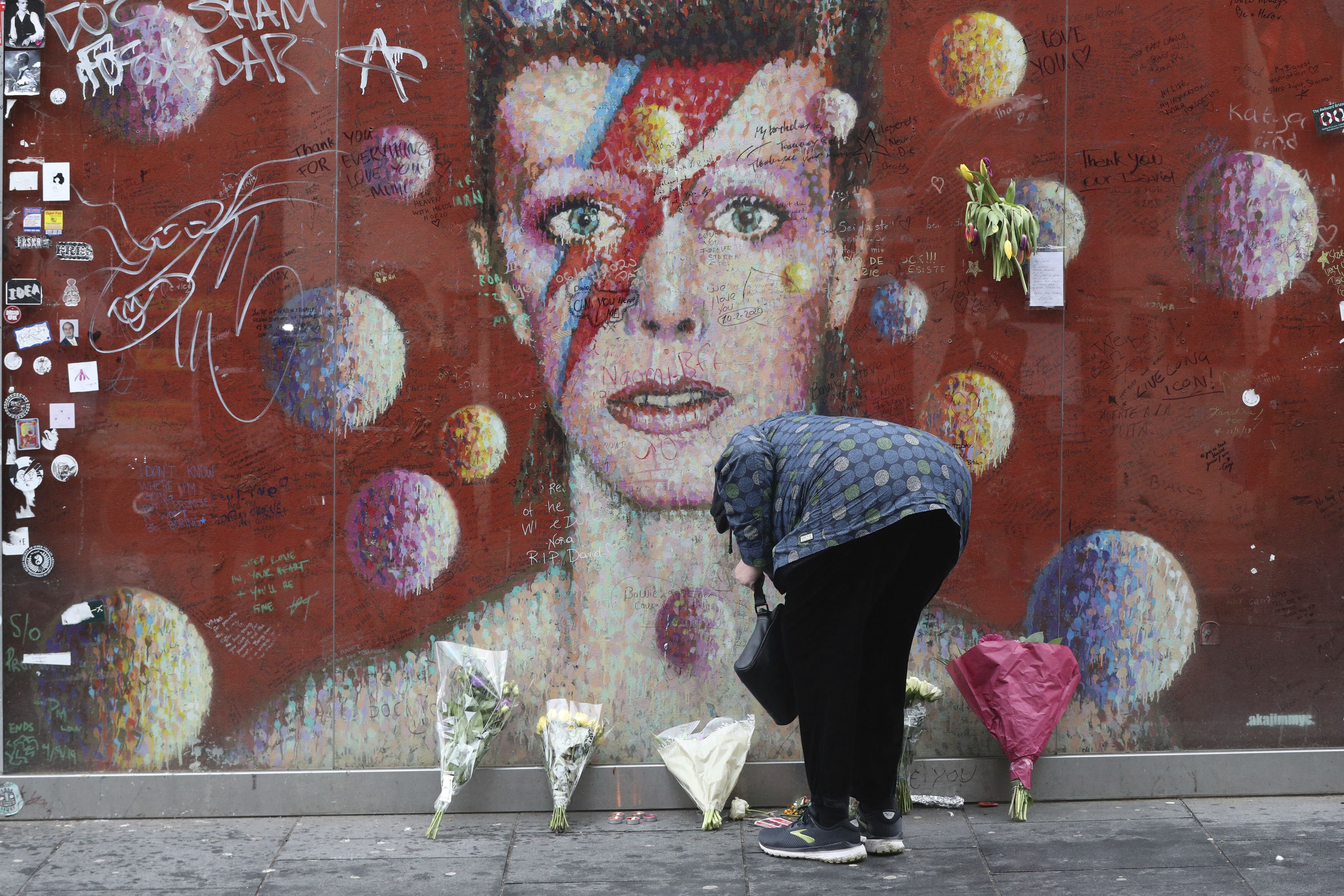 A woman lays a floral tribute at the David Bowie mural in Brixton, south London on the fifth anniversary of the singer's death, Sunday Jan. 10, 2021.  The singer-songwriter Bowie died of liver cancer at his home in New York, USA, on 10 January 2016. (Jonathan Brady/PA via AP)