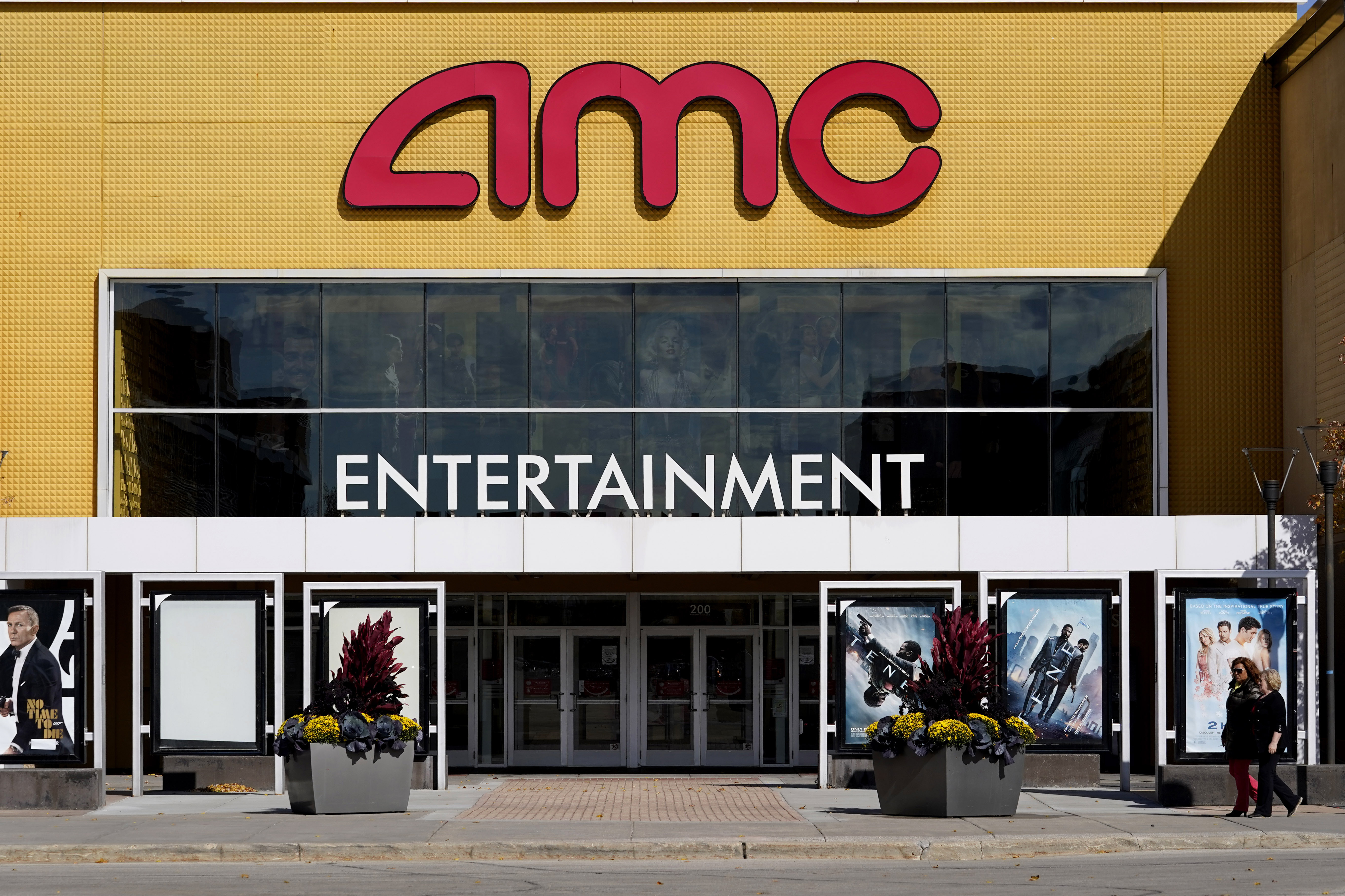 People walk past a AMC Randhurst 12 theater in Mount Prospect, Ill., Thursday, Oct. 15, 2020. AMC Theaters is warning investors that without a steady flow of movies to bring people into the remaining theaters it has open, the company could run out of cash by the end of 2020, during the COVID-19 pandemic. (AP Photo/Nam Y. Huh)