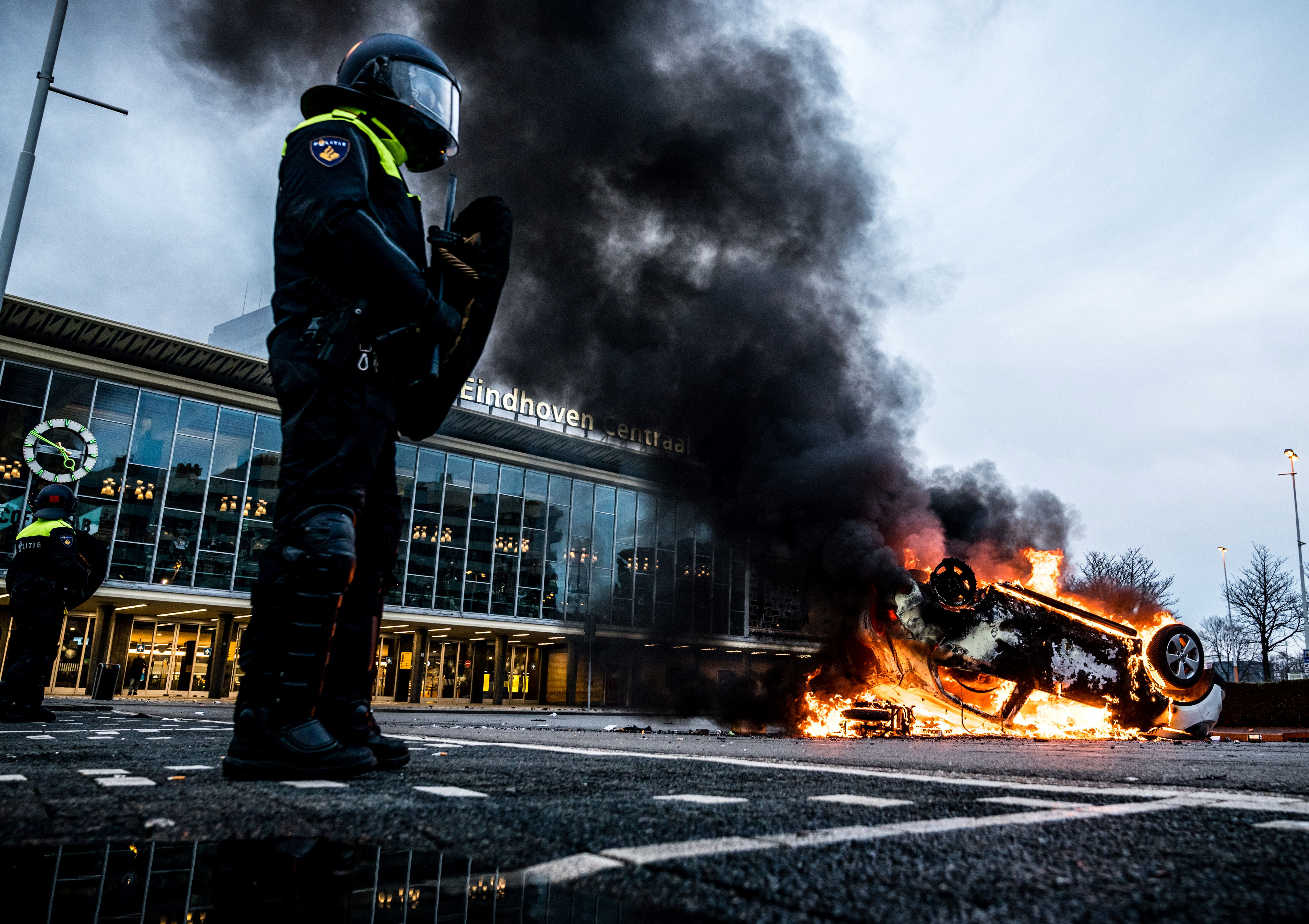 A car has been set on fire in front of the train station, on January 24, 2021 in Eindhoven, after a rally by several hundreds of people against the corona policy. (Photo by ROB ENGELAAR / various sources / AFP) / Netherlands OUT (Photo by ROB ENGELAAR/ANP/AFP via Getty Images)