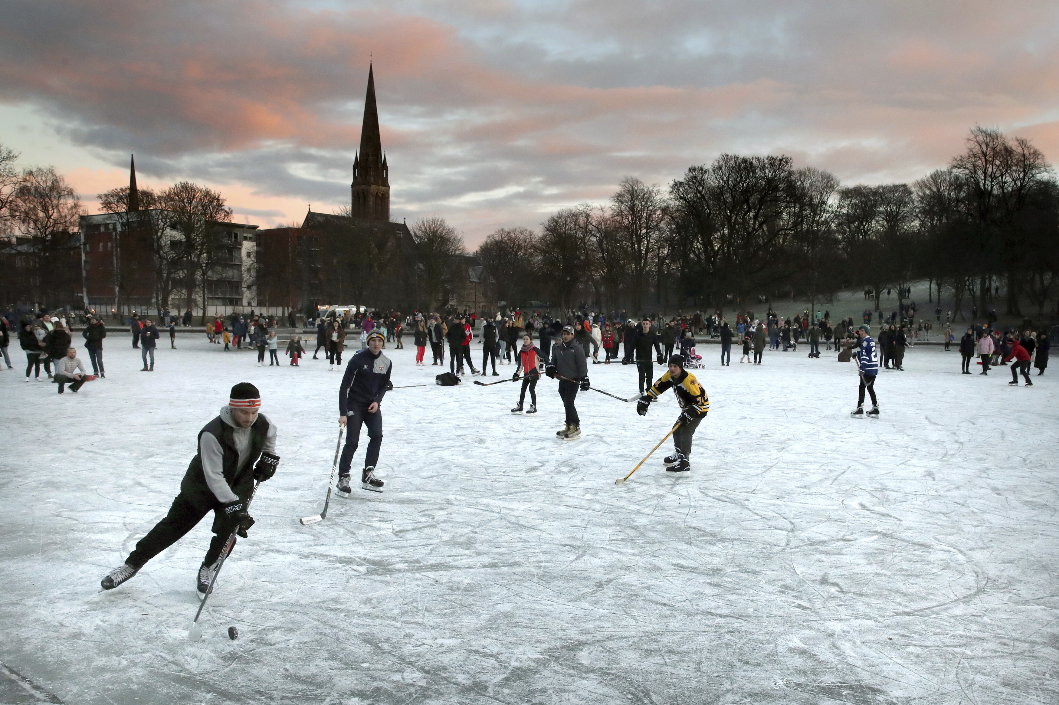 People play ice hockey as the sun sets on a frozen pond in Queen's Park, Glasgow, Scotland, Sunday Jan. 3, 2021. (Andrew Milligan/PA via AP)
