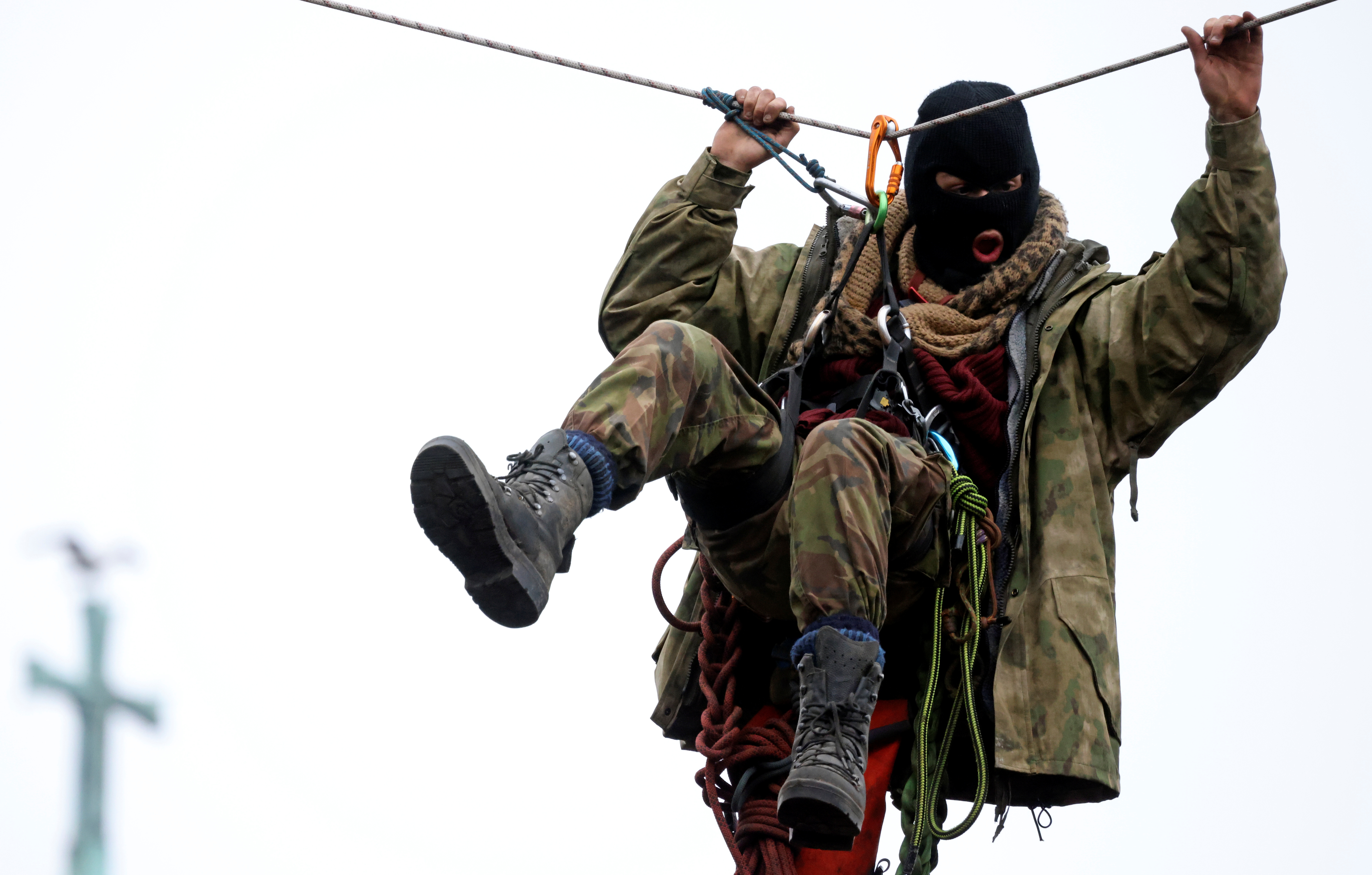 An Extinction Rebellion activist hangs from a rope at a makeshift camp, as others occupy tunnels under Euston Square Gardens, to protest against the HS2 high-speed railway in London, Britain, January 27, 2021. REUTERS/Hannah McKay