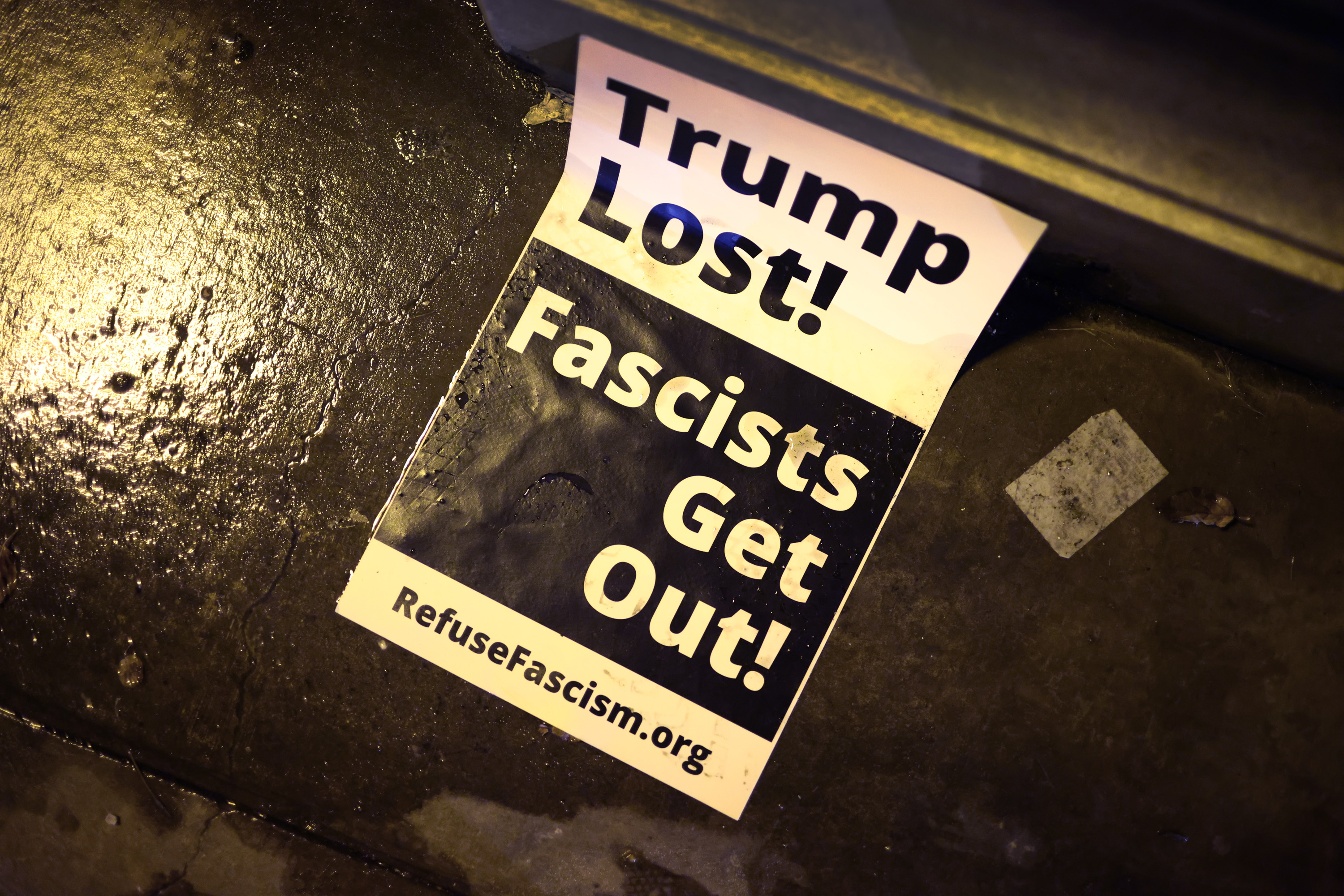CHICAGO, ILLINOIS - JANUARY 07: A protest sign rests on the ground near a small group of demonstrators protesting near Trump Tower on January 07, 2021 in Chicago, Illinois. Protesters called for the removal of President Donald Trump from office after a pro-Trump mob stormed the Capitol building in Washington, DC yesterday as lawmakers met to count the Electoral College votes in the presidential election.  (Photo by Scott Olson/Getty Images)