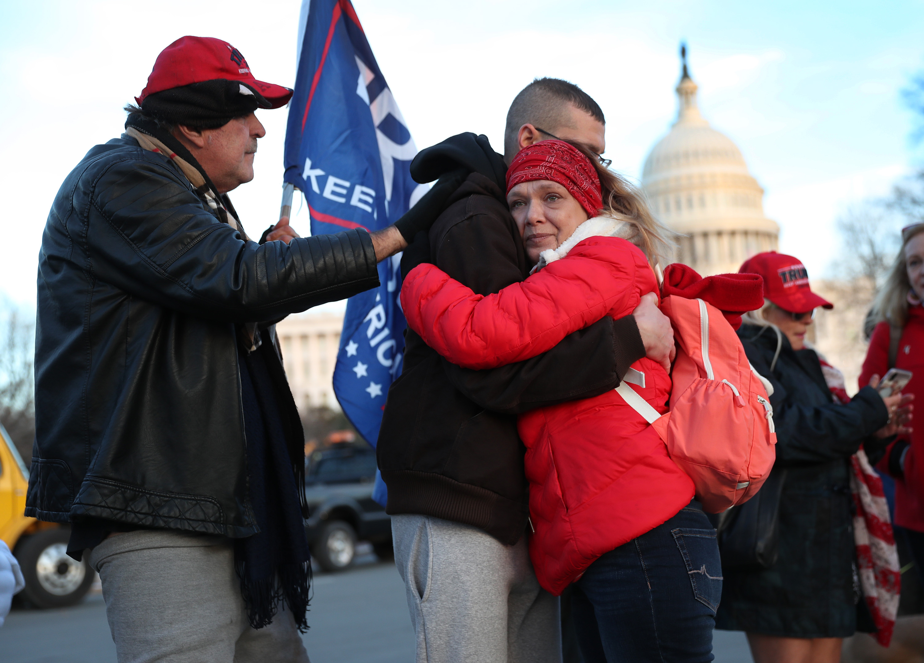WASHINGTON, DC - JANUARY 07: (L-R) Gary Phaneuf, Tony Naples and Melody Black share a moment together as they visit a memorial setup near the U.S. Capitol Building for Ashli Babbitt who was killed in the building after a pro-Trump mob broke in on January 07, 2021 in Washington, DC. Congress finished tallying the Electoral College votes and Joe Biden was certified as the winner of the 2020 presidential election. (Photo by Joe Raedle/Getty Images)