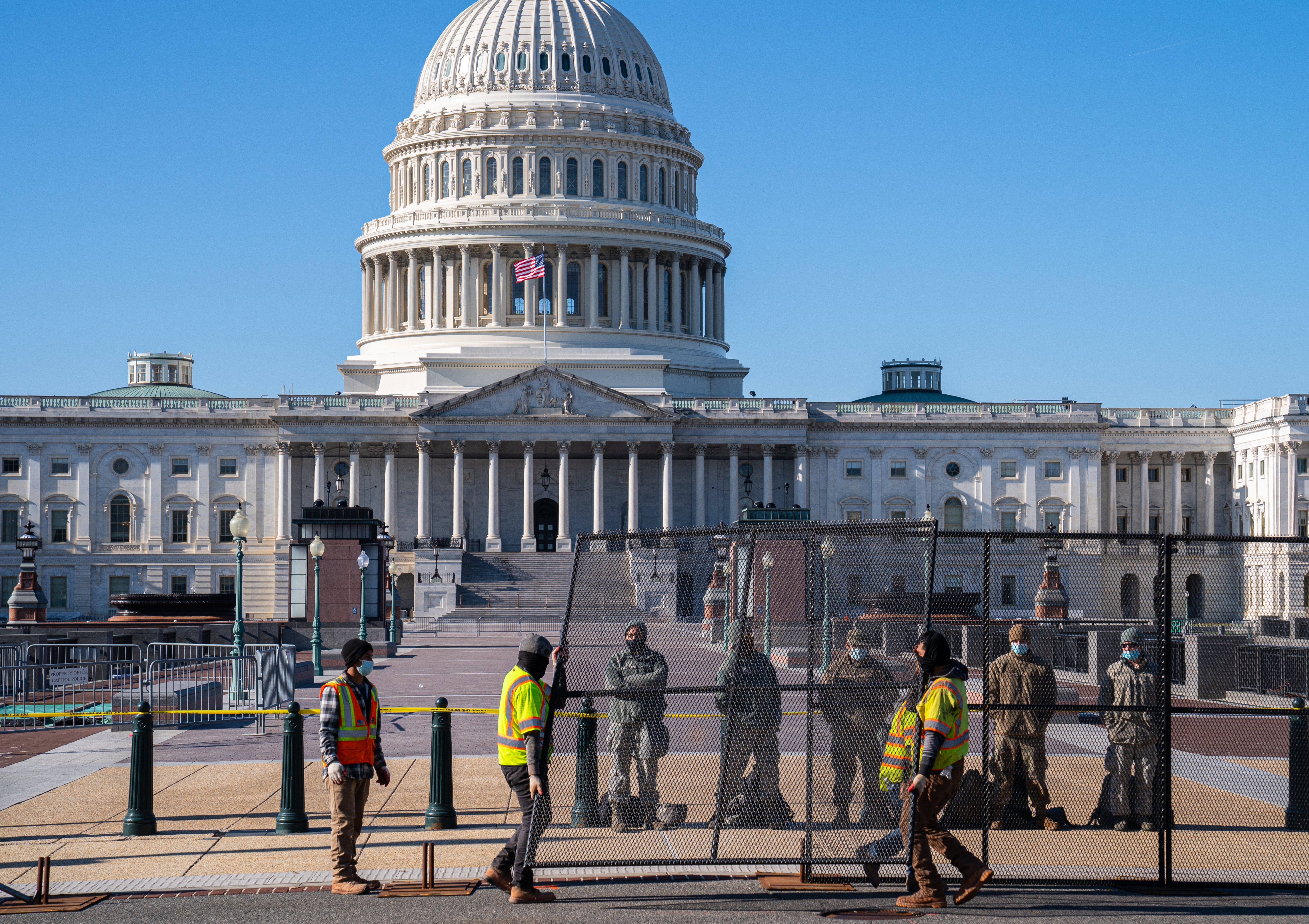 WASHINGTON, DC - JANUARY 07: National Guard members stand behind a construction crew as they assemble wire barricades surrounding the U.S. Capitol on January 7, 2021 in Washington, DC. A pro-Trump mob stormed and desecrated the building the day before as Congress held a joint session to ratify President-elect Joe Biden's 306-232 Electoral College win over President Donald Trump. (Photo by Robert Nickelsberg/Getty Images)