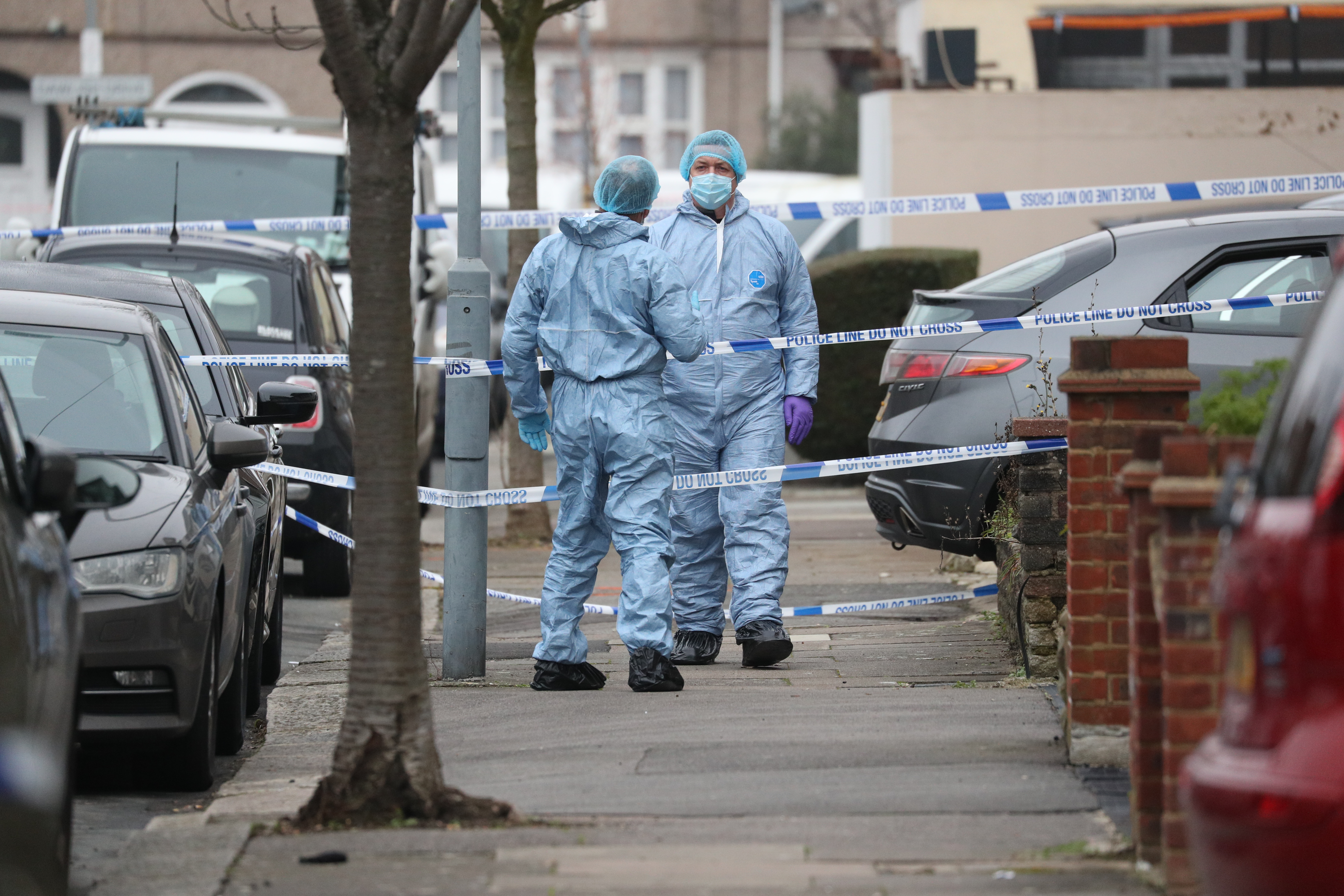 Forensic officers at the scene in Tavistock Gardens, Ilford, east London after two men died at a property in the street. The men were found seriously injured on Sunday morning and died at the scene, said the Metropolitan Police. A woman, who had non life-threatening injuries, was arrested at the scene and taken to hospital for treatment.