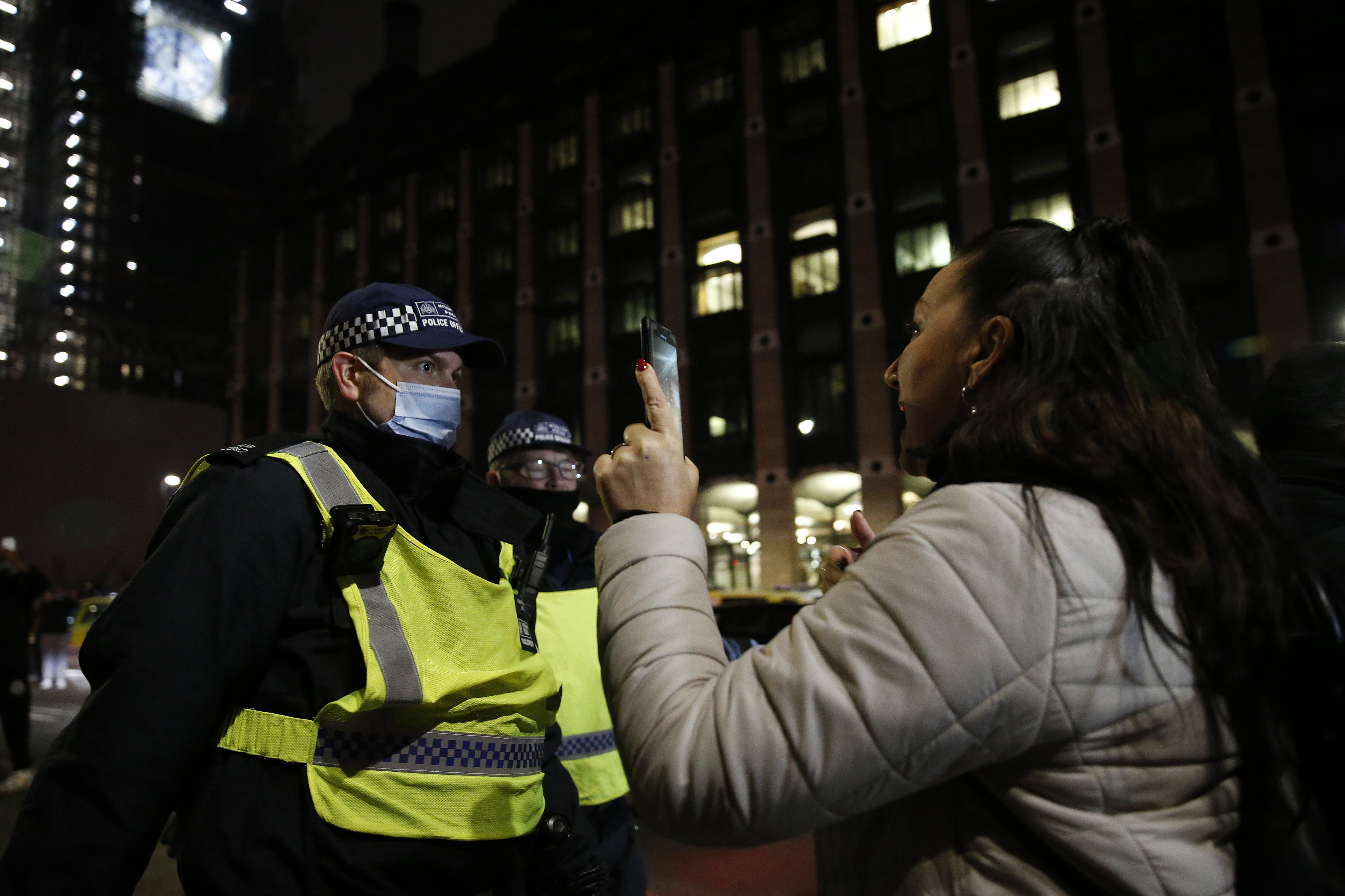 LONDON, ENGLAND - JANUARY 1: Met Police officers attempt to disperse crowds gathered near Westminster Bridge on January 1, 2021 in London, United Kingdom. New Year's Eve Celebrations have been curtailed in the UK this year dues to Coronavirus pandemic restrictions. With most of the UK in tiers three and four socialising is off limits. (Photo by Hollie Adams/Getty Images)