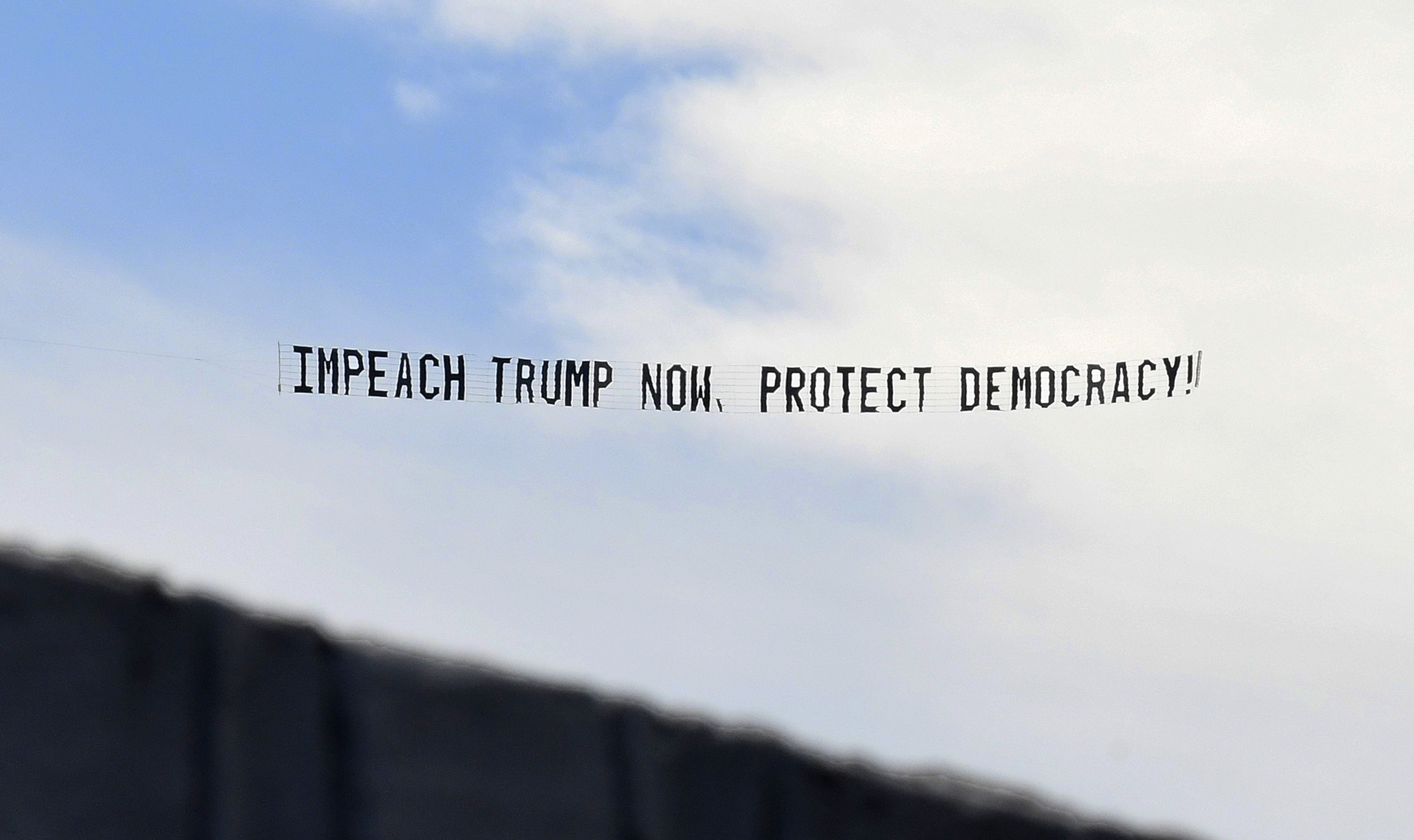 ORLANDO, FLORIDA, UNITED STATES - 2021/01/07: A banner towed by a plane calls for the impeachment of U.S. President Donald Trump.  A day after a pro-Trump mob stormed the U.S. Capitol, members of the House Judiciary Committee have announced articles of impeachment for President Donald Trump, alleging he will remain a threat to national security, democracy and the Constitution if he is allowed to remain in office for two more weeks. (Photo by Paul Hennessy/SOPA Images/LightRocket via Getty Images)