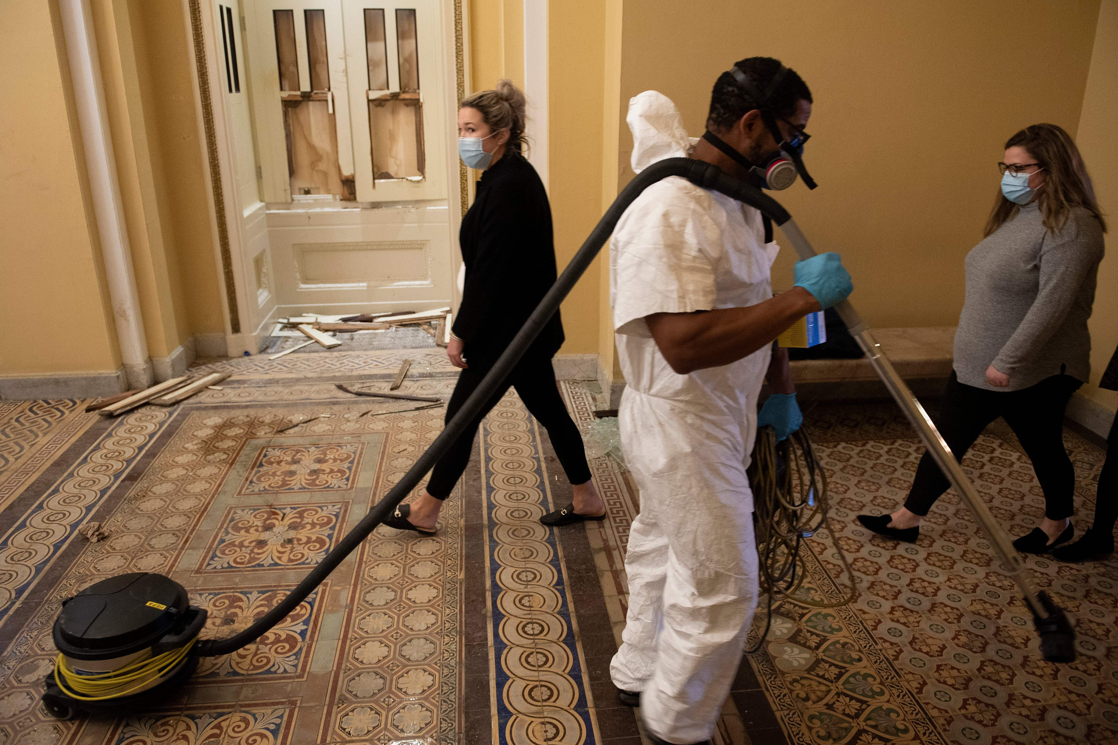 A worker walks while clearing damage a day after a pro-Trump mob broke into the US Capitol January 7, 2021, in Washington, DC. (Photo by Brendan Smialowski / AFP) (Photo by BRENDAN SMIALOWSKI/AFP via Getty Images)