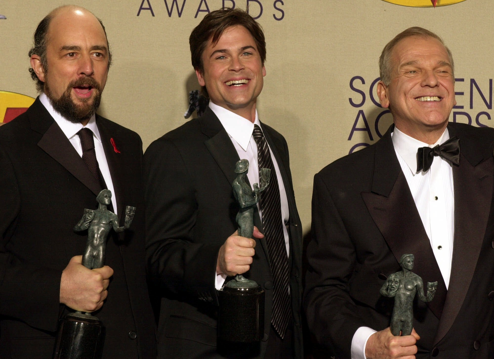 """Members of the cast of """"The West Wing"""" from left: Richard Schiff, Rob Lowe and John Spencer hold their awards for outstanding performance by an ensemble in a drama series at the 7th annual Screen Actors Guild Awards, Sunday, March 11, 2001, in Los Angeles. (AP Photo/Michael Caulfield)"""