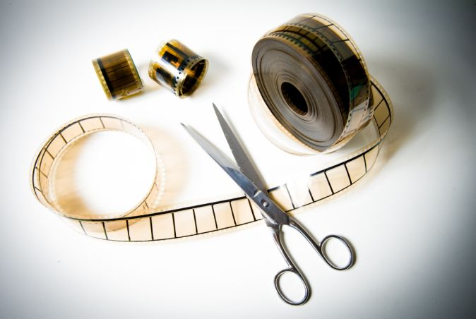 A 35mm movie film reel cutted with scissors on white background and color effect