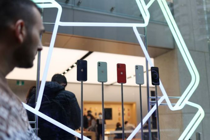 FILE PHOTO: A shopper looks at an iPhone 12 display while waiting in line to enter an Apple Store in the city centre as the state of New South Wales continues to report low case numbers of the coronavirus disease (COVID-19) in Sydney, Australia, October 26, 2020. REUTERS/Loren Elliott