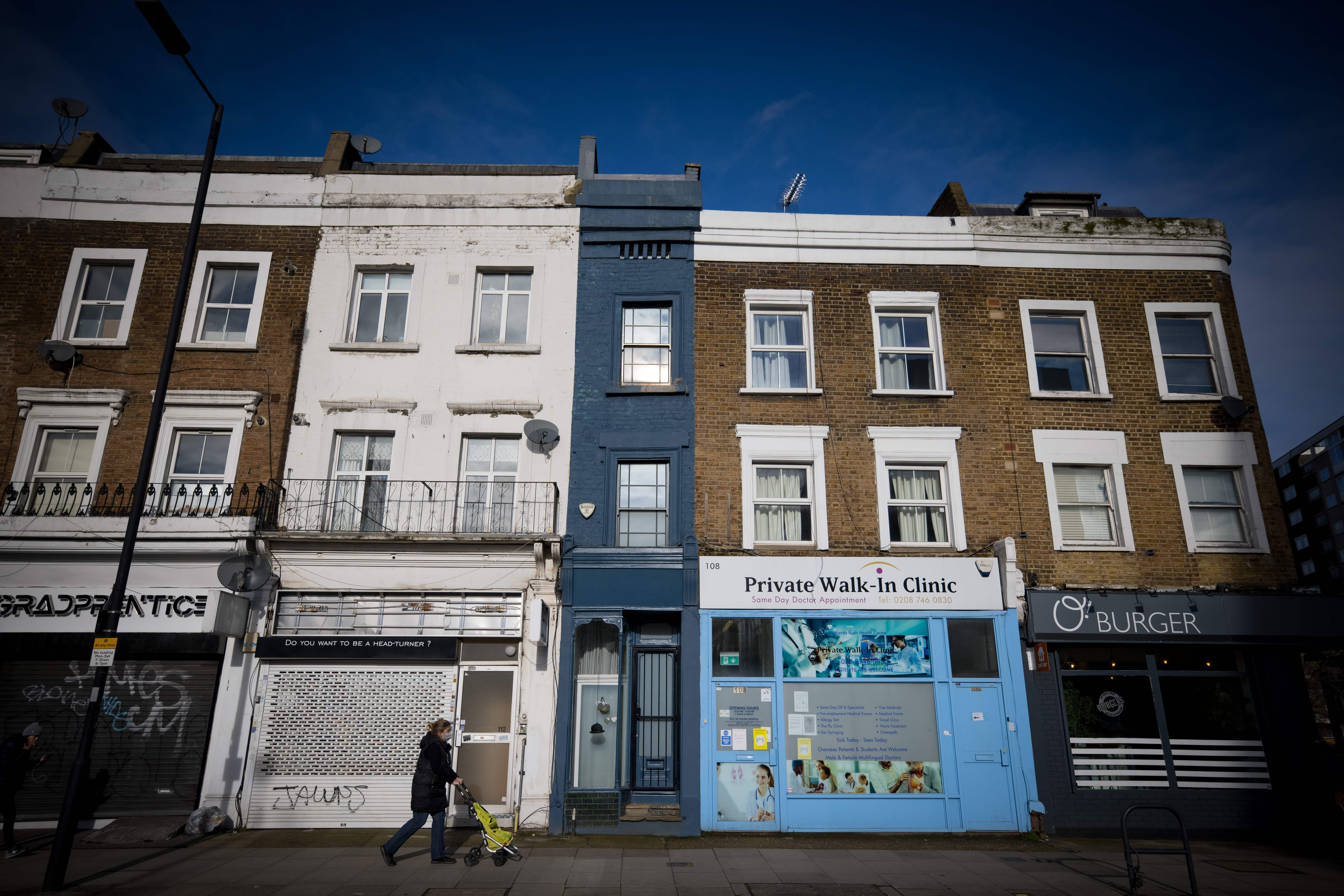 A pedestrian passes the front of what is dubbed 'London's thinnest house' (painted blue) in west London on February 5, 2021. - Wedged neatly between a doctor's surgery and a shuttered hairdressing salon, the five floor house in Shepherds Bush is just 5ft 6ins (1.6 metres) at its narrowest point and is currently on the market for £950,000 ($1,300,000, 1,100,000 euros). The unusual property, originally a Victorian hat shop with storage for merchandise and living quarters on its upper floors, was built sometime in the late 19th or early 20th century. (Photo by Tolga Akmen / AFP) (Photo by TOLGA AKMEN/AFP via Getty Images)