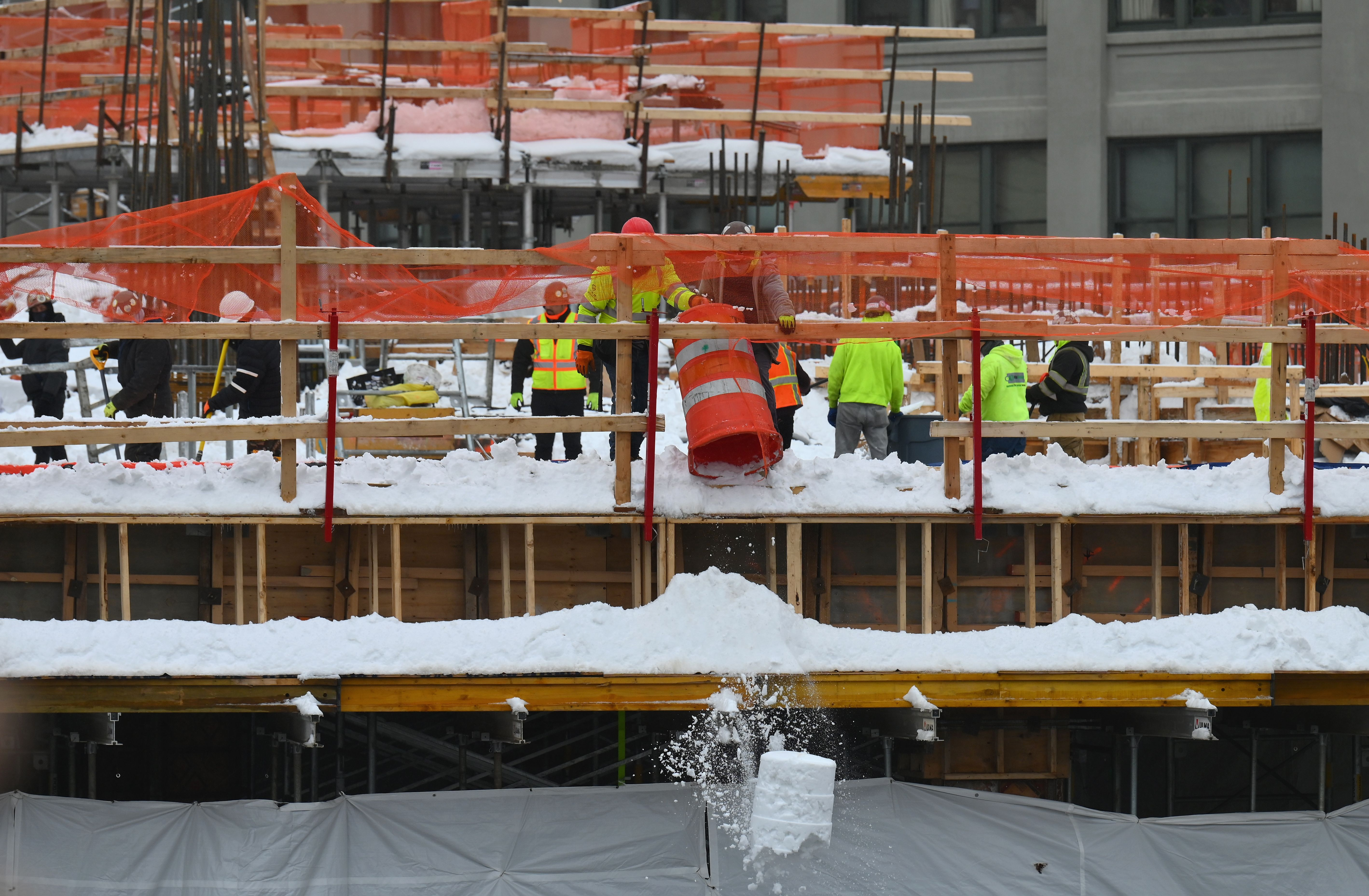 Construction workers free a building construction site of snow in the Brooklyn Borough of New York on February 2, 2021. - A huge snowstorm has brought chaos to the United States' east coast, shuttering airports, closing schools and forcing the postponement of coronavirus vaccinations into Tuesday morning as New York City steeled itself for possibly one of its heaviest ever snowfalls. New York declared a state of emergency restricting non-essential travel, moved all children back to remote learning and rescheduled long-awaited vaccine shots as some parts of the city were hit by more than 18 inches (1.5 feet) of snow. CNN meteorologists said that figure could reach two feet before the storm comes to an end. (Photo by Angela Weiss / AFP) (Photo by ANGELA WEISS/AFP via Getty Images)