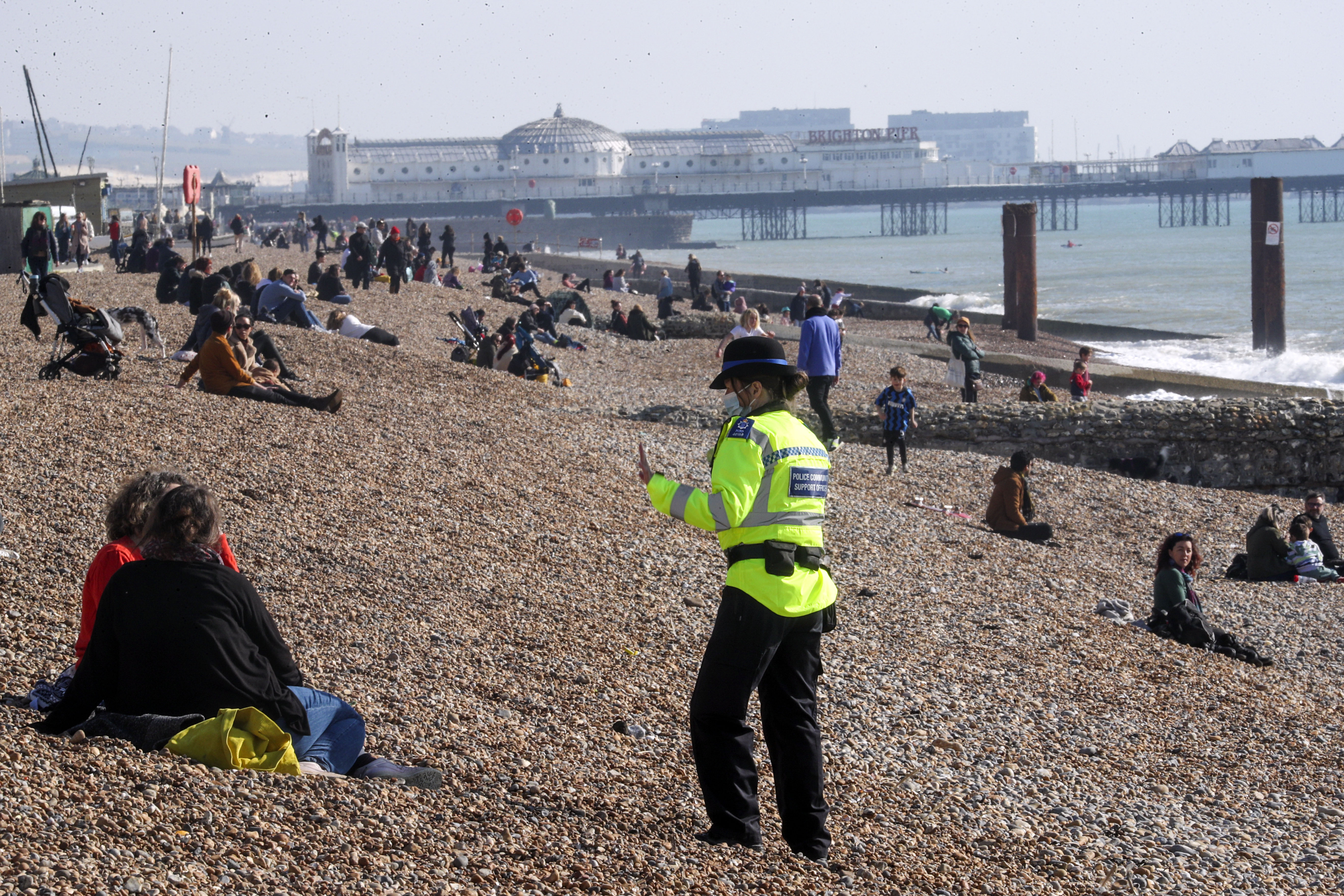 <p>A community support officer speaks to people enjoying the sunshine on Brighton beach in Sussex. Picture date: Sunday February 28, 2021.</p>