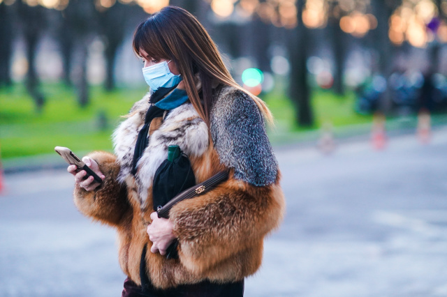 PARIS, FRANCE - JANUARY 25: A guest wears a blue protective face mask, a brown and gray fluffy faux fur winter coat, a Chanel bag, outside the Grand Palais, during Paris Fashion Week - Haute Couture Spring/Summer 2021, on January 25, 2021 in Paris, France. (Photo by Edward Berthelot/Getty Images)