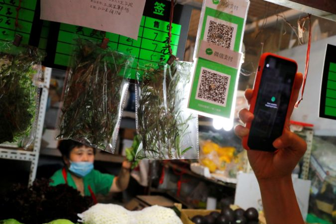 A person scans the QR code of the digital payment services WeChat Pay at a fresh market in Beijing, China August 8, 2020. REUTERS/Thomas Peter - RC2H9I9YYSZD