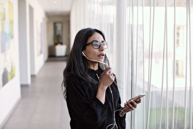 Businesswoman talking on smart phone while standing by window in corridor at office