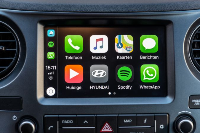 Alkmaar, The Netherlands - September 26, 2018: Apple CarPlay main screen in modern car dashboard. CarPlay is an Apple standard that enables a car radio or head unit to be a display and controller for an iPhone.