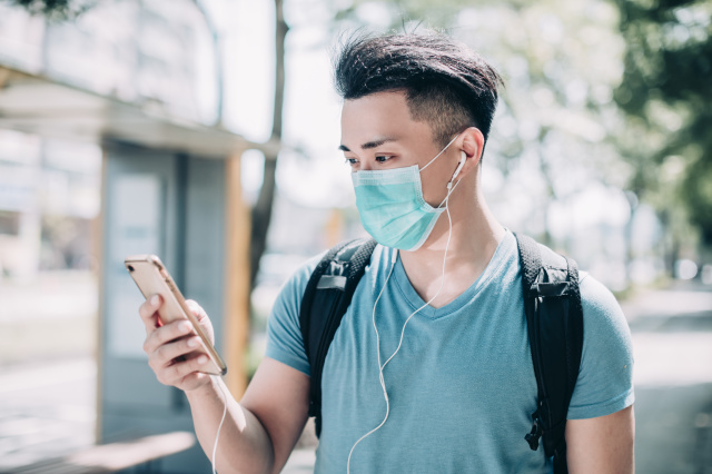 young man wear mask and walking on street using mobile phone