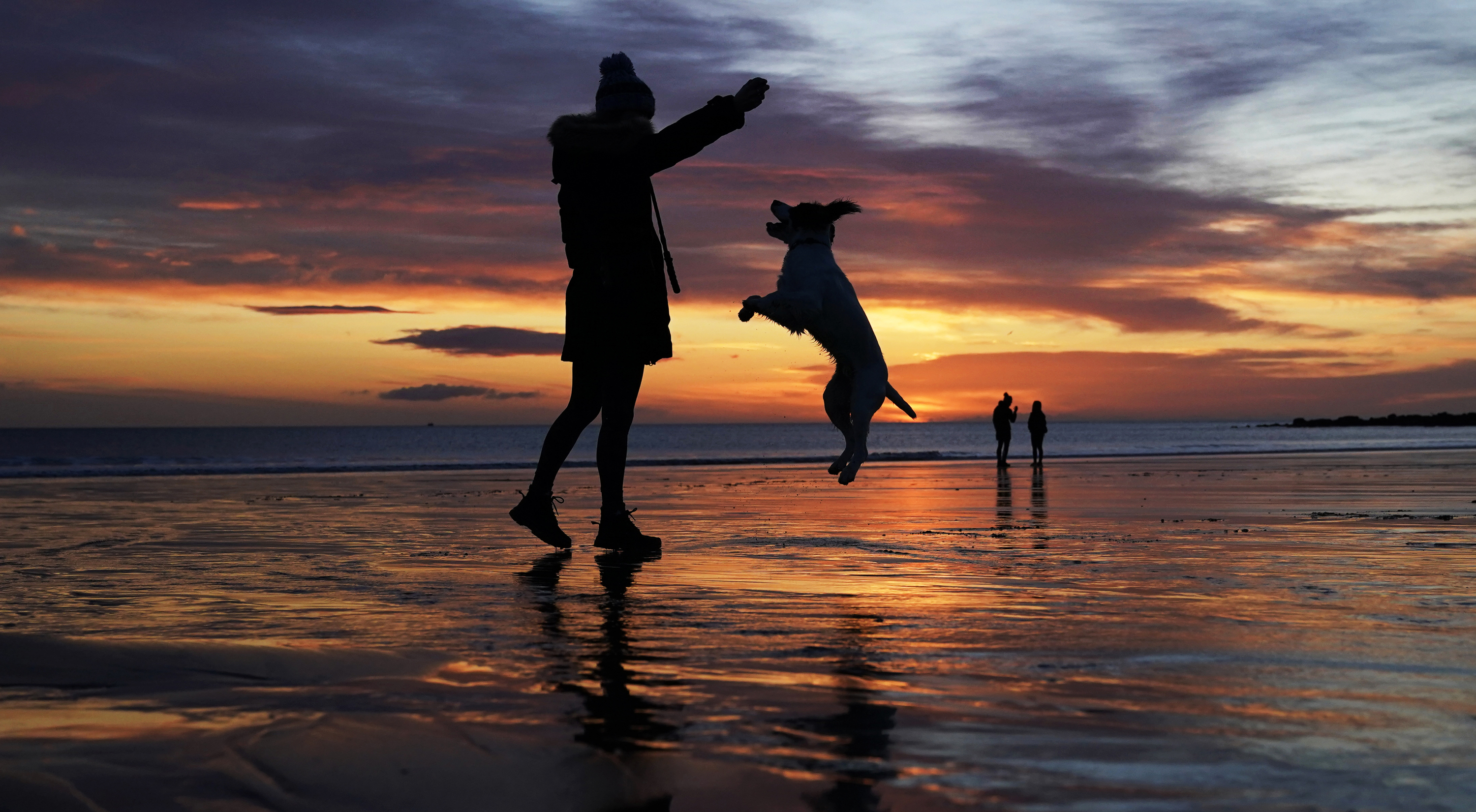 <p>A woman throws a ball for her dog as the sun rises at Tynemouth Longsands beach in Tyne and Wear on the North East coast. Picture date: Friday March 12, 2021.</p>