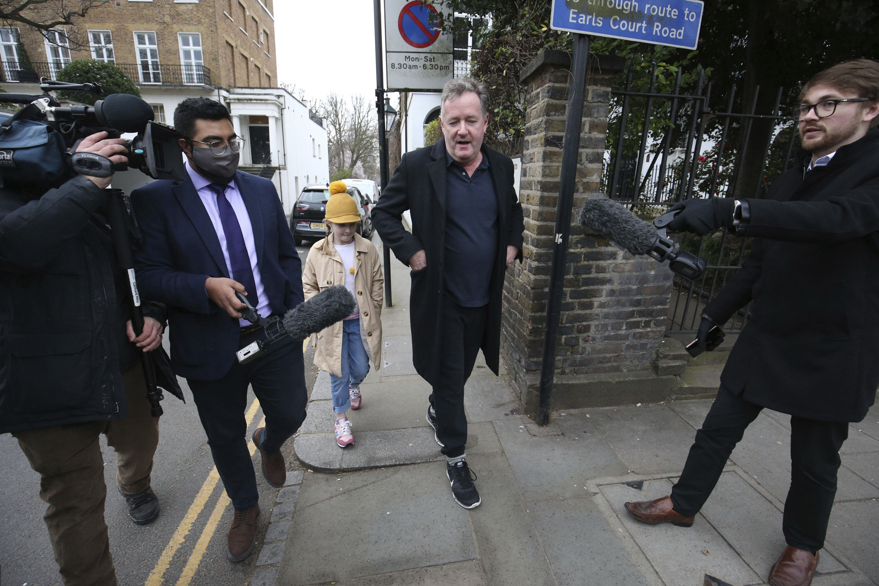 """<p>British television host Piers Morgan speaks to reporters outside his home in Kensington, central London, as he walks his daughter Elise to school on Wednesday March 10, 2021. Morgan quit the """"Good Morning Britain"""" program on Tuesday after making controversial comments about the Duchess of Sussex. The U.K.'s media watchdog said earlier Tuesday it was launching an investigation into the show under its harm and offense rules after receiving more than 41,000 complaints about Morgan's comments on Meghan. (Jonathan Brady/PA via AP)</p>"""