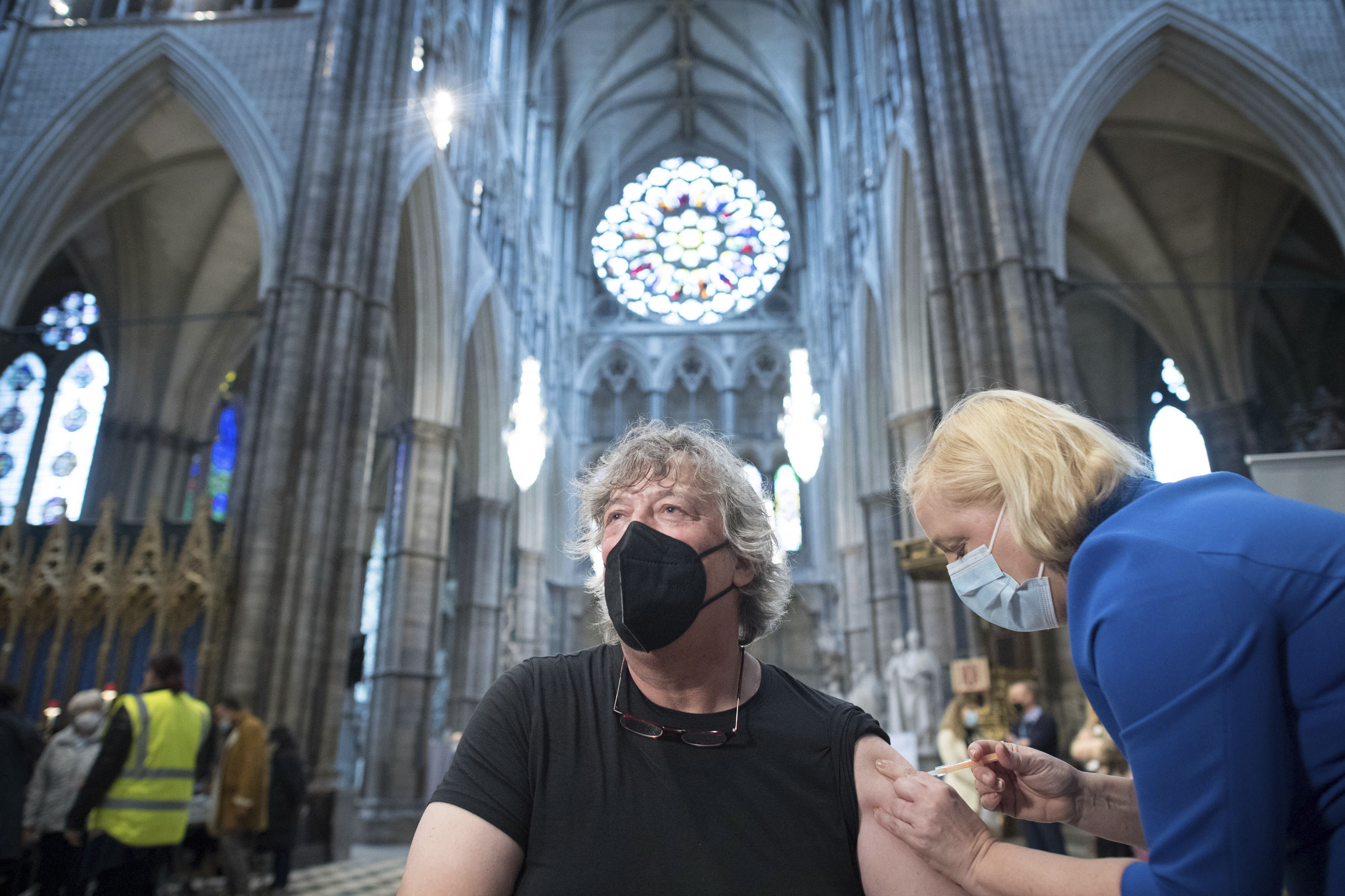 <p>Actor Stephen Fry receives a COVID-19 jab, at a new vaccination site, at Poets' Corner in Westminster Abbey, London, Wednesday March 10, 2021. (Stefan Rousseau/PA via AP)</p>